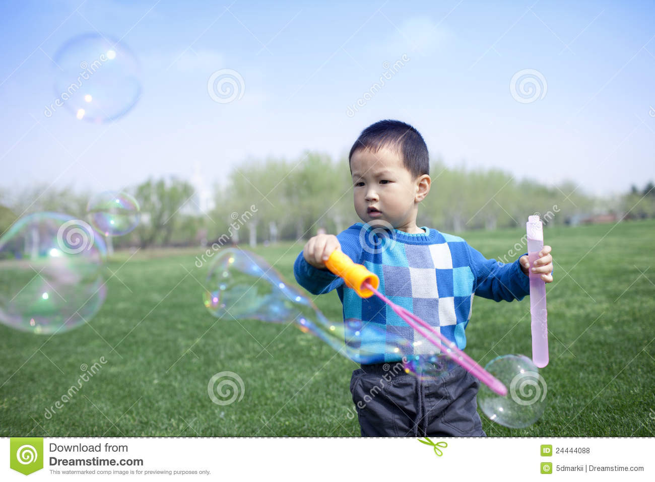 Asian Chinese boy blowing soap bubbles