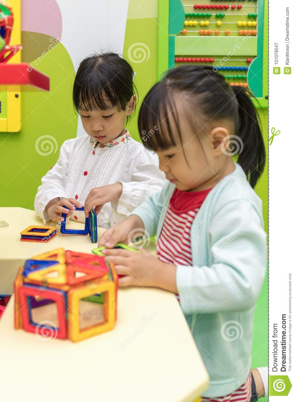 Asian Chinese little girls playing colorful magnet plastic block