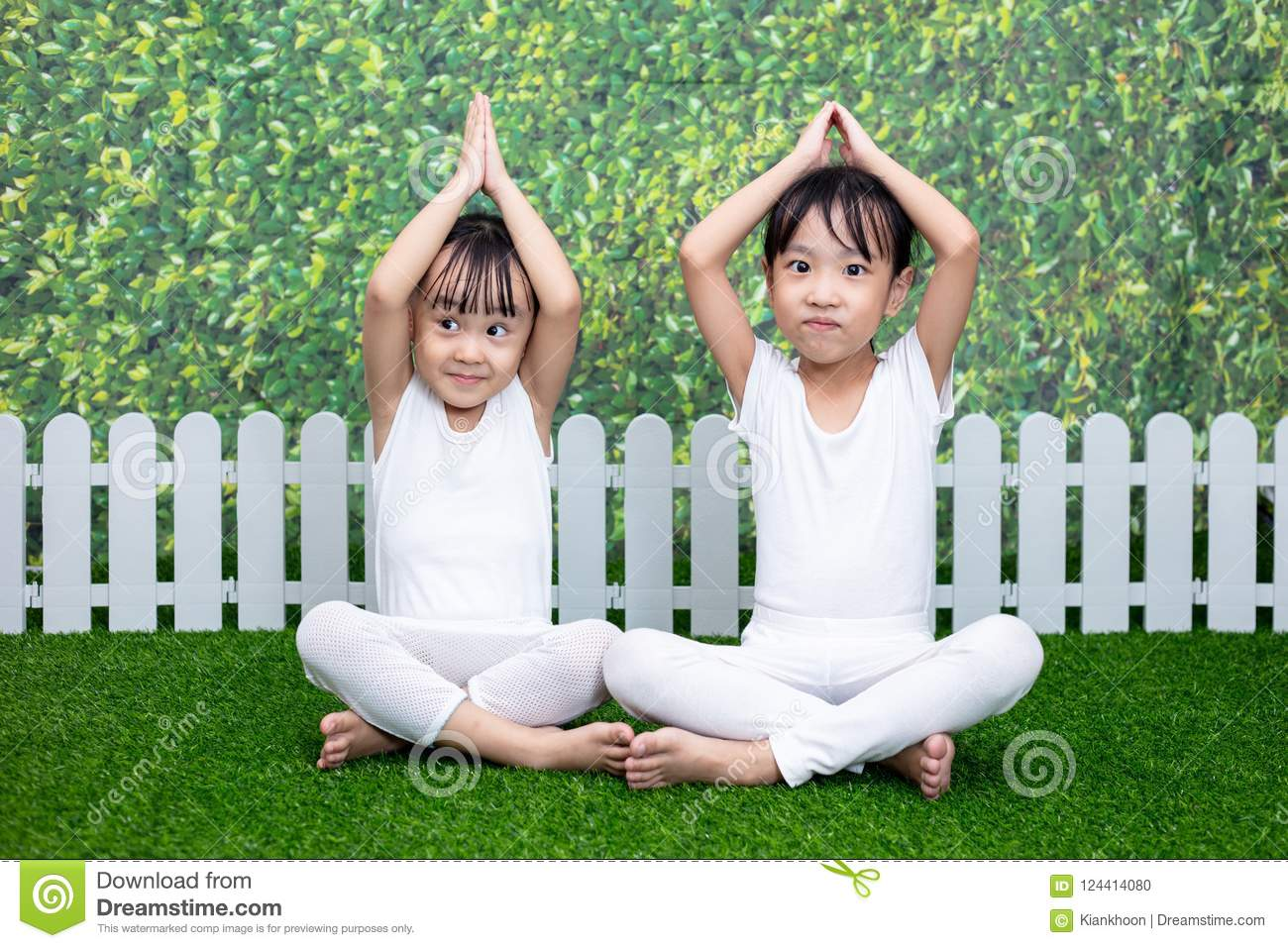 Asian Chinese little girls practicing yoga pose on a mat