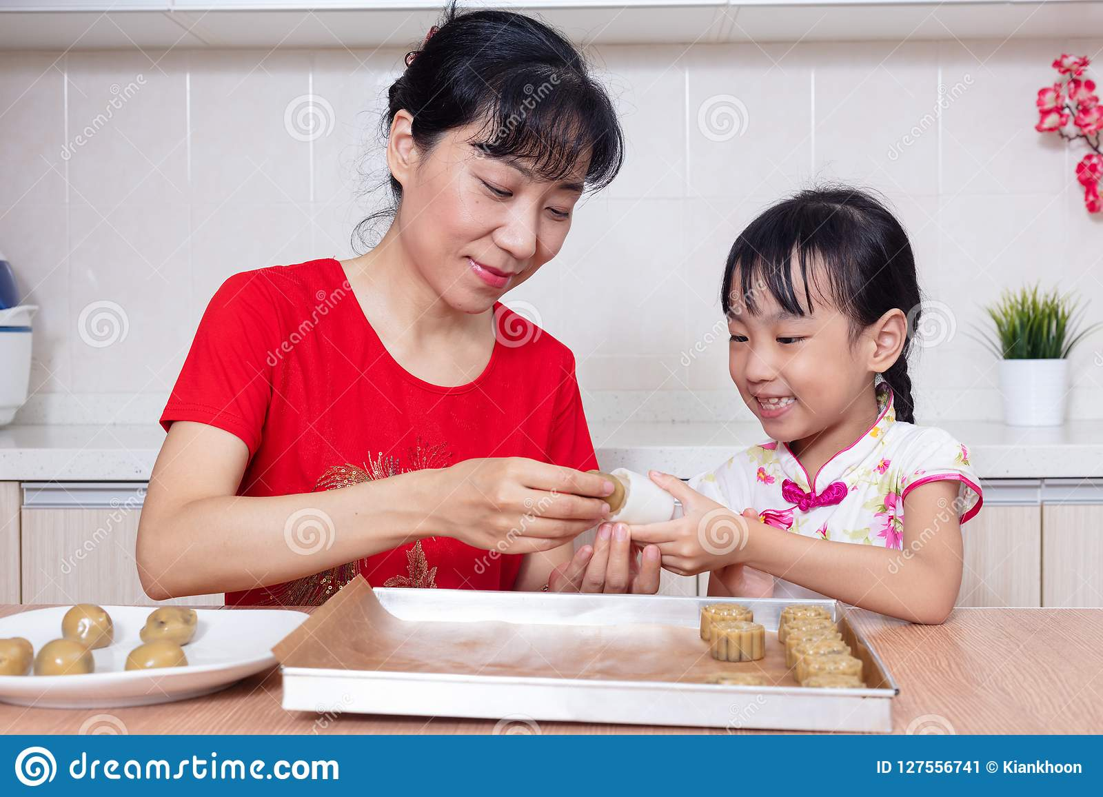 asian chinese mother and daughter making moon cake in the kitche