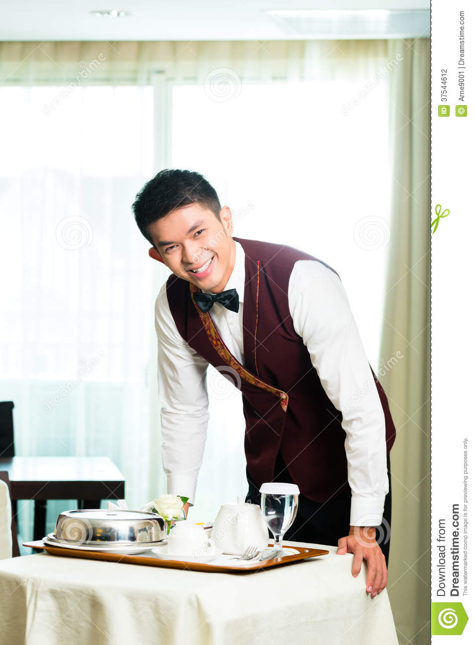 Asian Chinese room service waiter or steward serving guests food in a ...