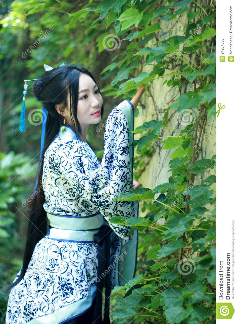 Asian Chinese woman in traditional Blue and white Hanfu dress, play in a famous garden near wall