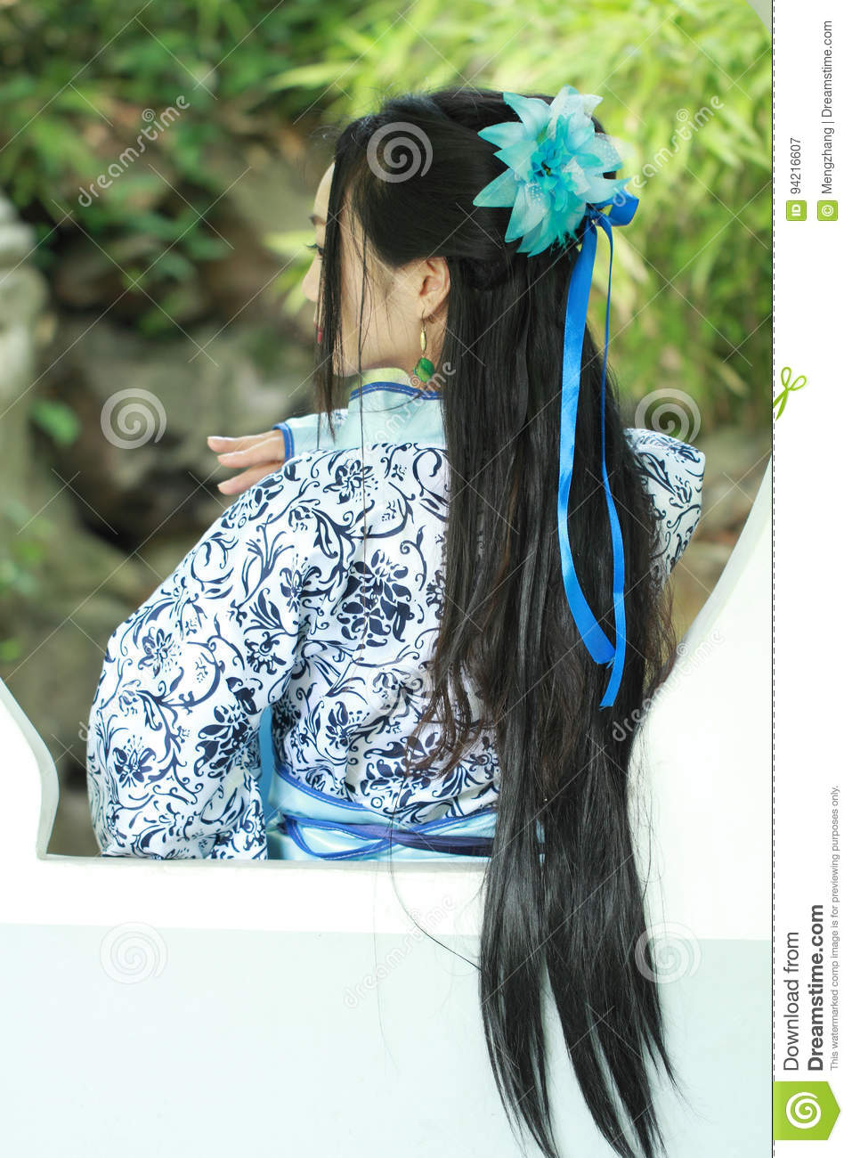 Asian Chinese woman in traditional Blue and white Hanfu dress, play in a famous garden ,Stand in front of the window