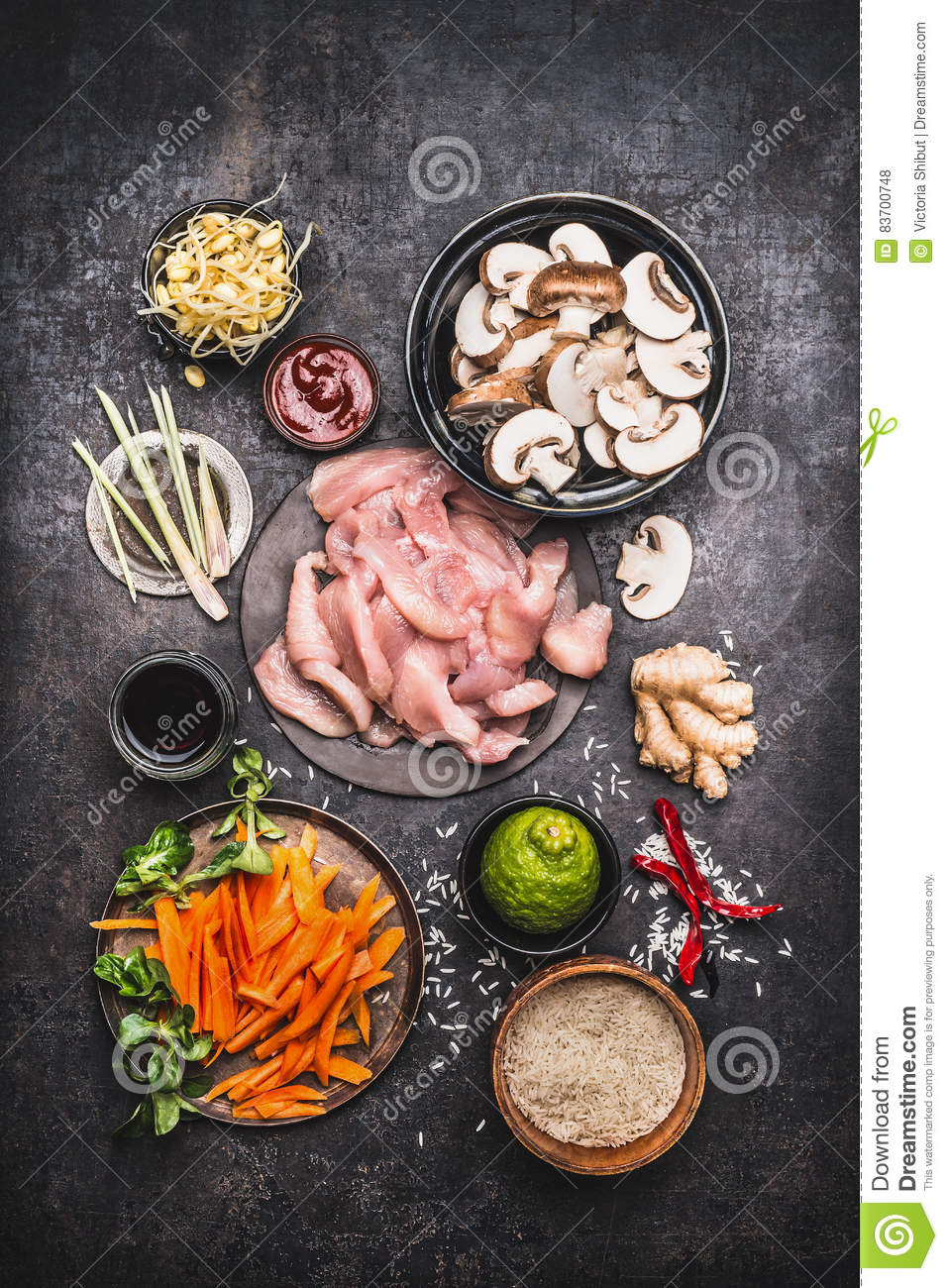 Asian Cooking Ingredients For Chicken Rice Dish With Vegetables On Dark Rustic Background , Top View Stock Photo