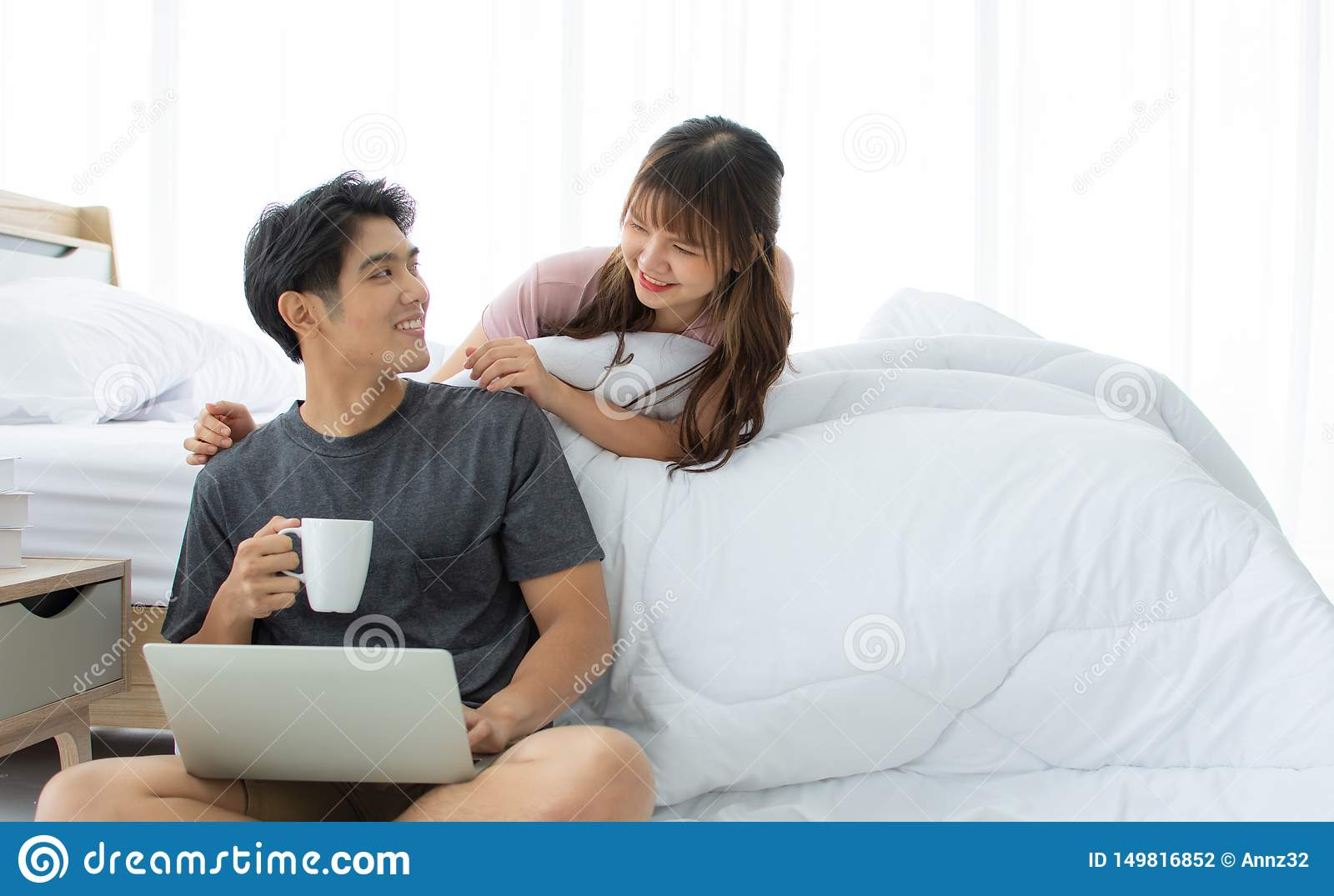 An Asian couple is taking rest in the bedroom