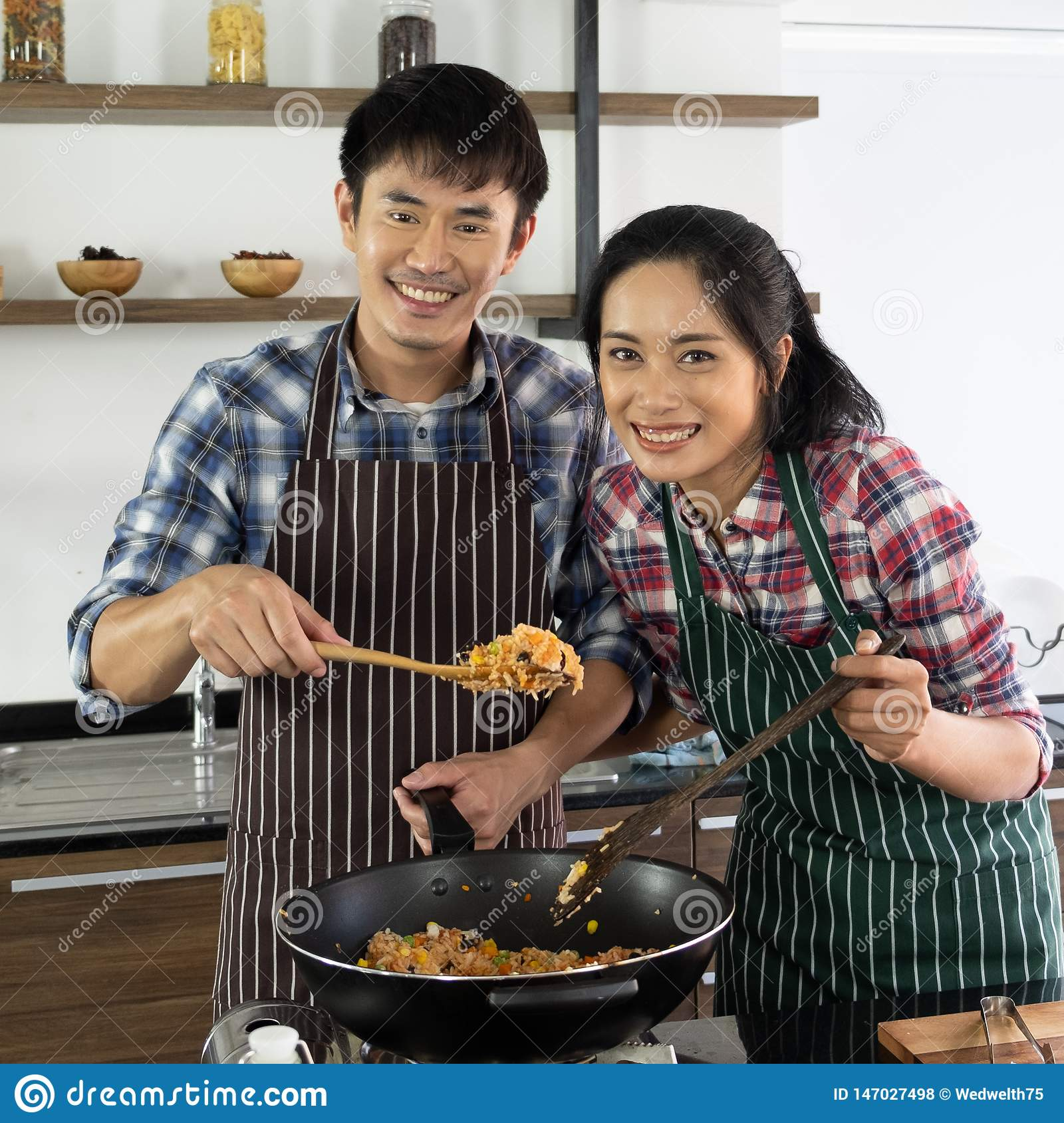 Asian couple are happy to cook together in the morning