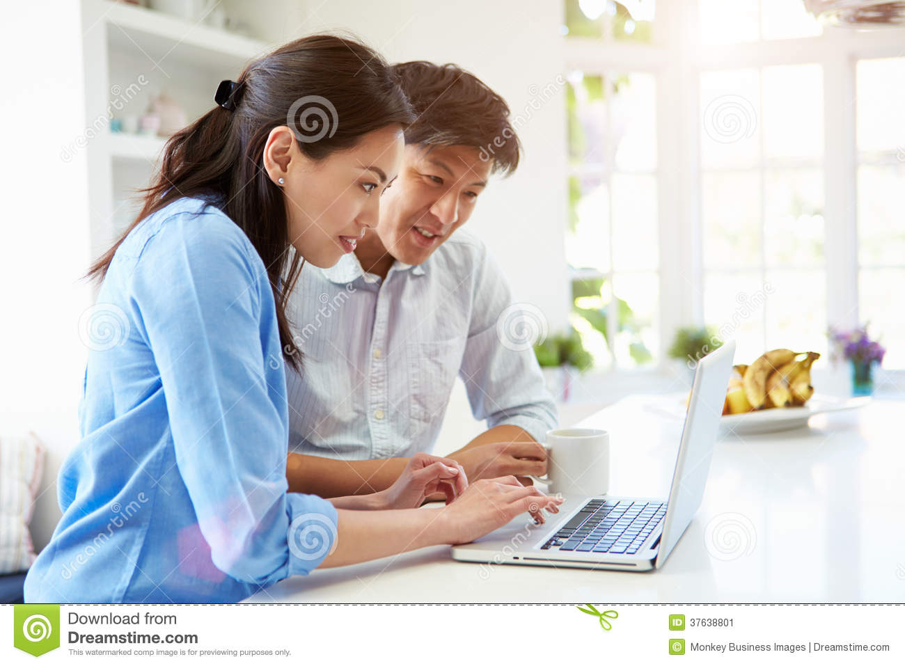 Asian Couple Looking At Laptop In Kitchen Stock Image - Image of ...
