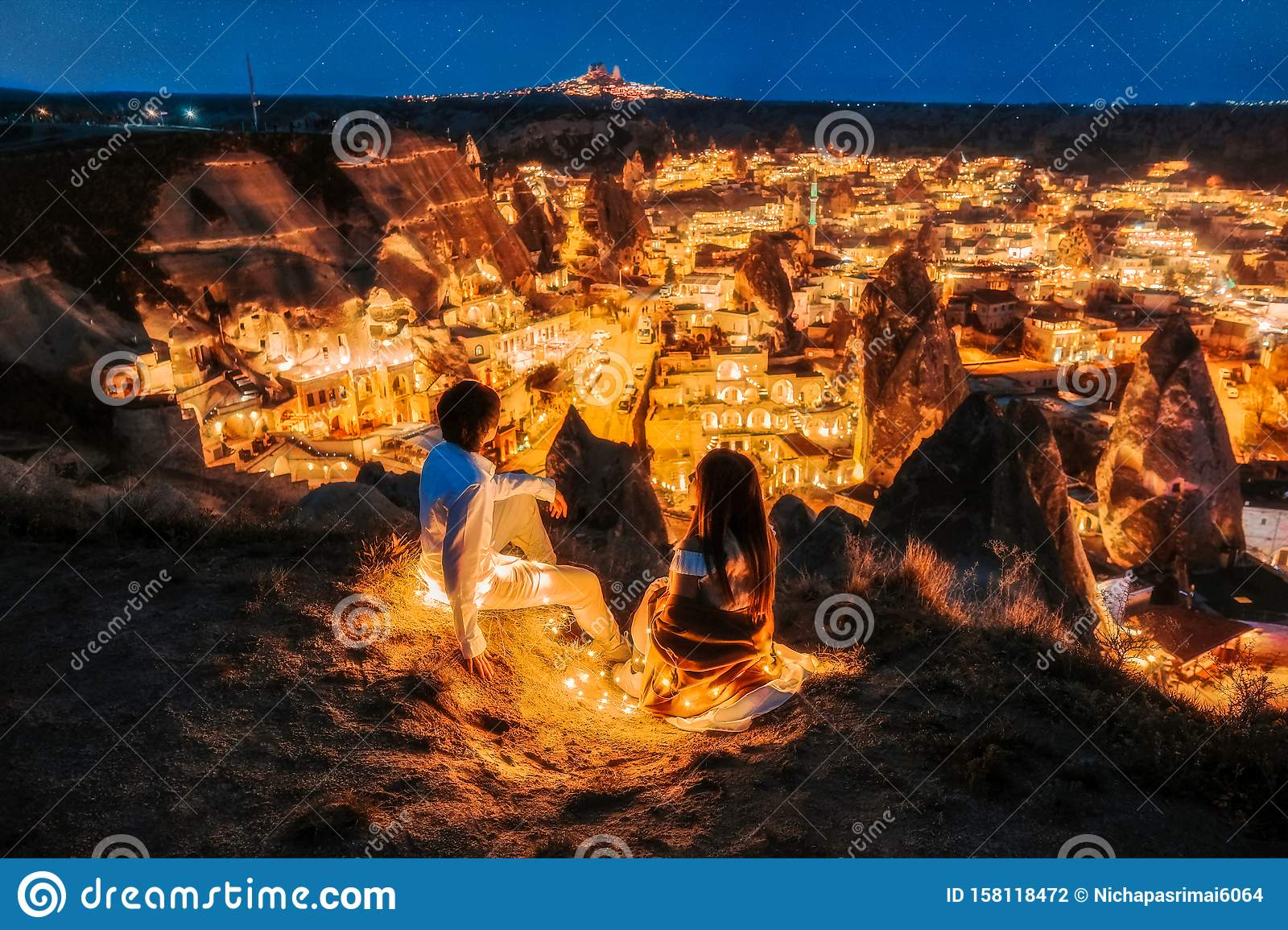Asian Couple in love and looking night view of Uchisar Goreme sunset view point ,Cappadocia. Nevsehir Province Turkey. This