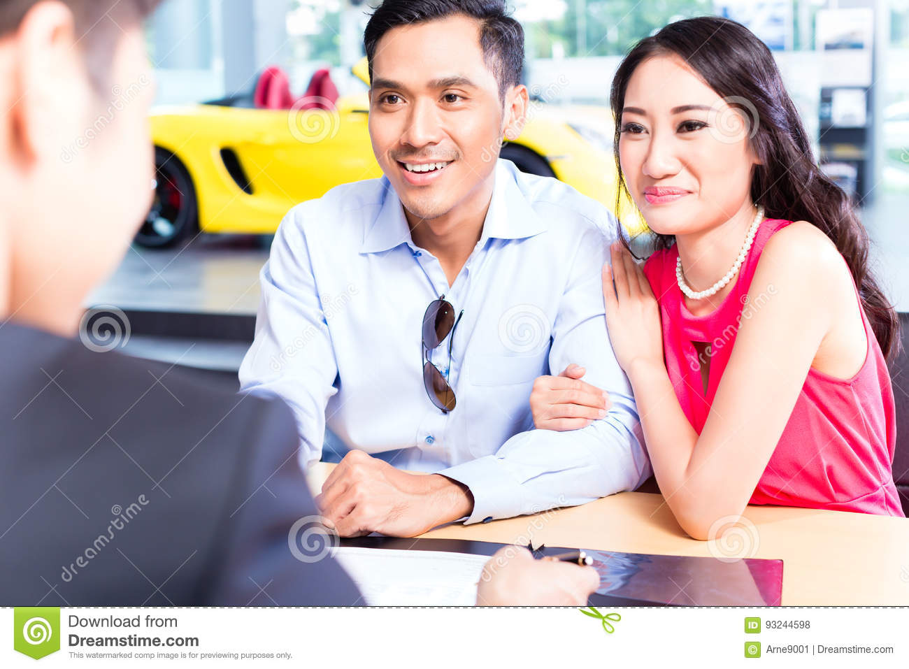 asian couple signing sales contract for car at dealership stock