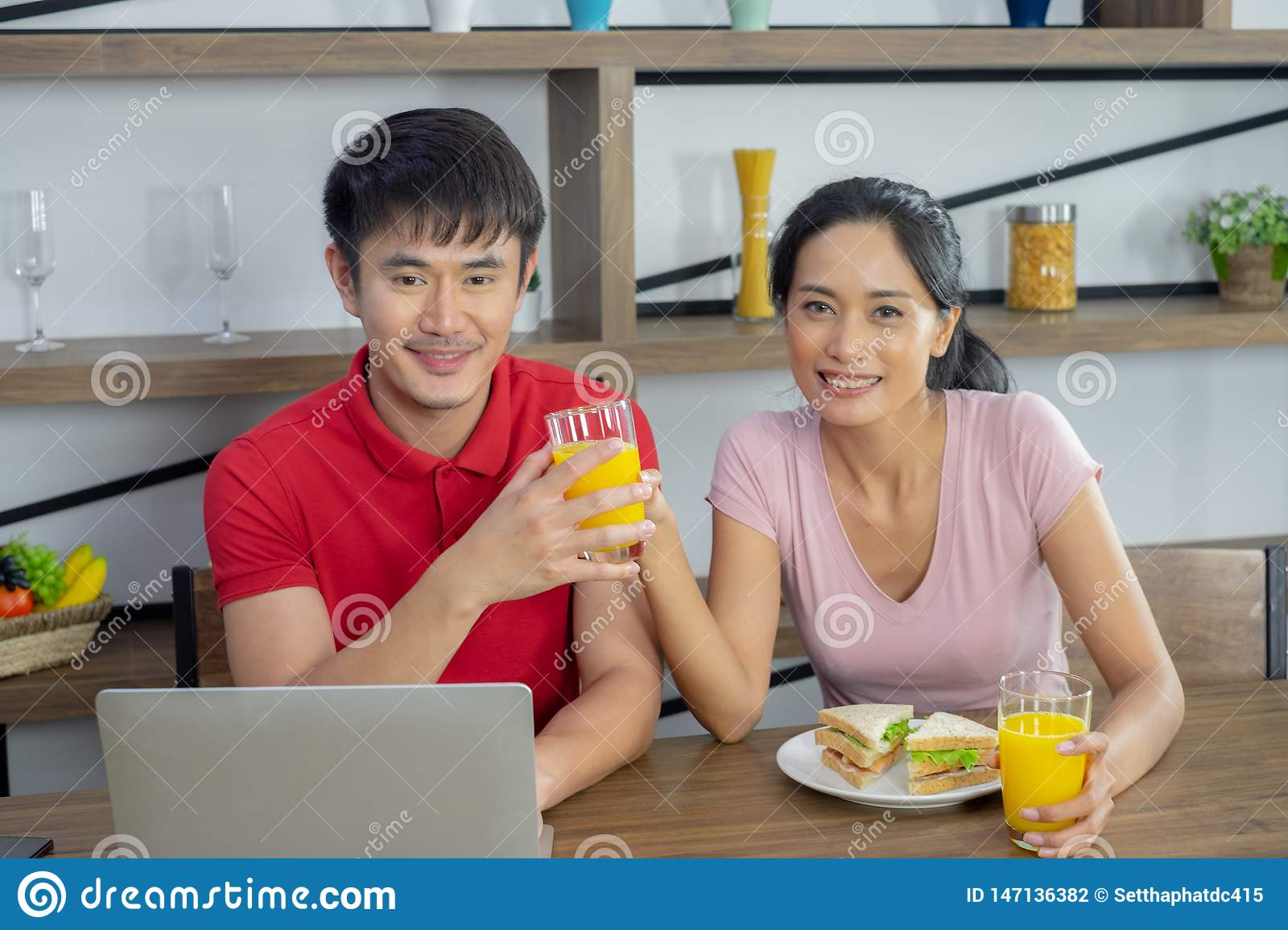 Asian couple, sitting at the dining table. Both of them are smiling happily. woman send the glass of orange juice to the male. And