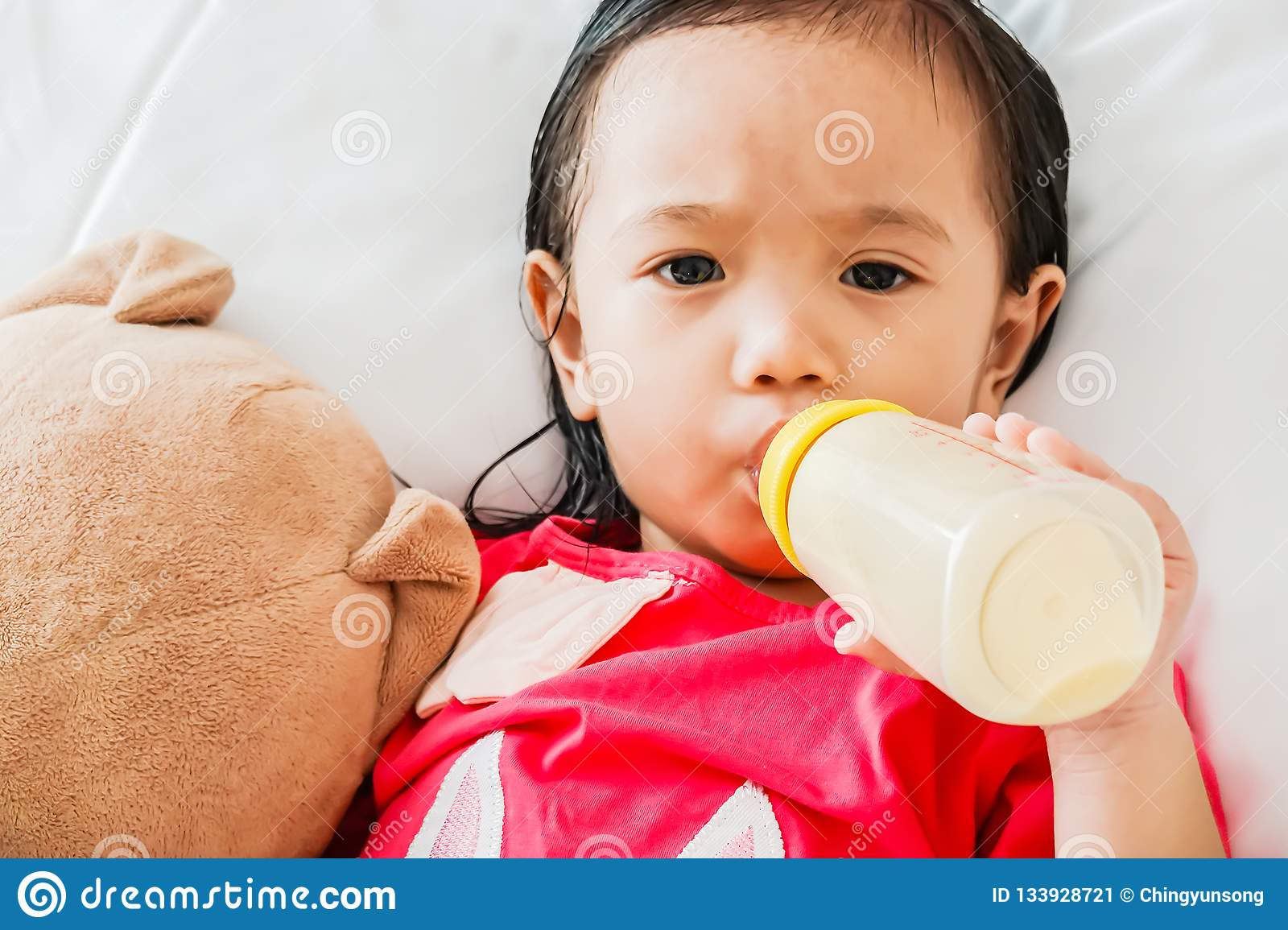 Asian cute baby girl drinking milk from bottle and sleeping on bed