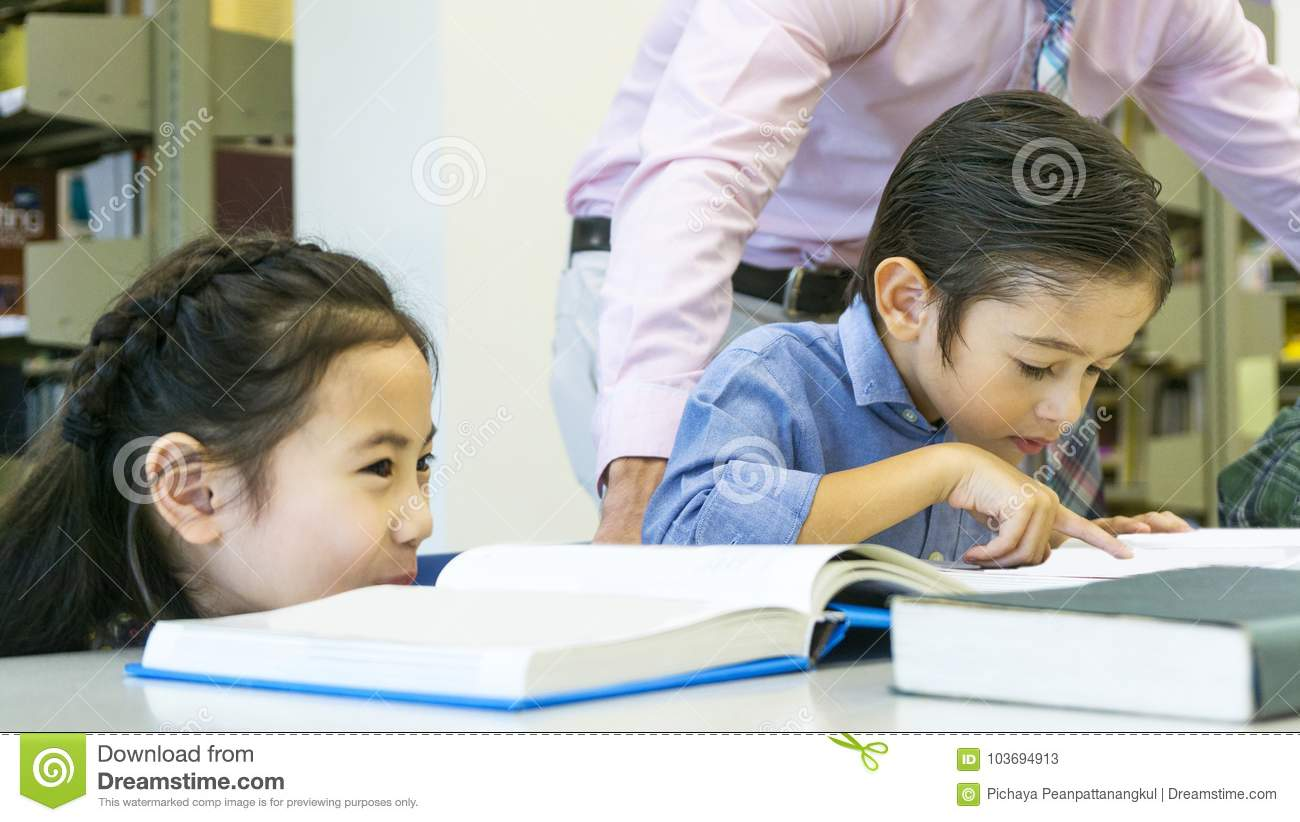 asian cute girl sitting and seeing the friend kid reading the bo