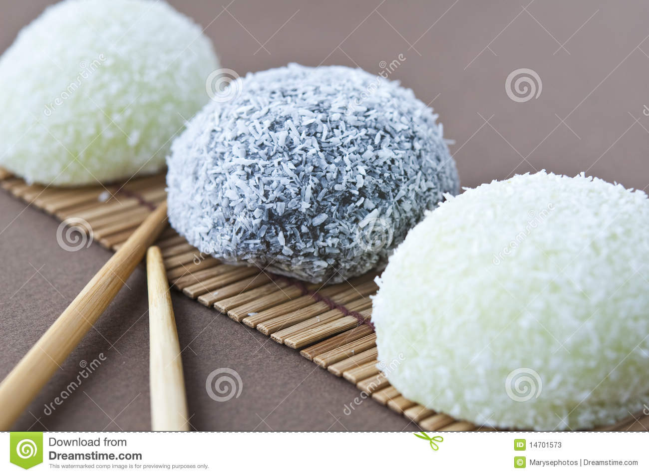 Asian dessert and chopsticks on brown background.