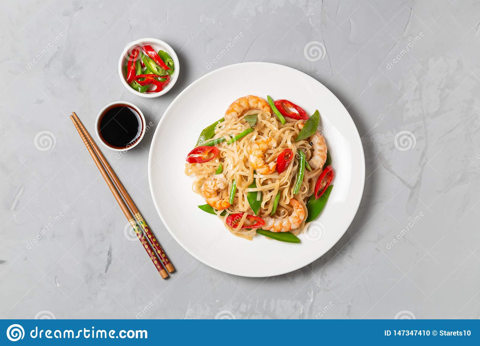 Asian dish of fried rice noodles with shrimp and vegetables. The view from the top. Copy-space.