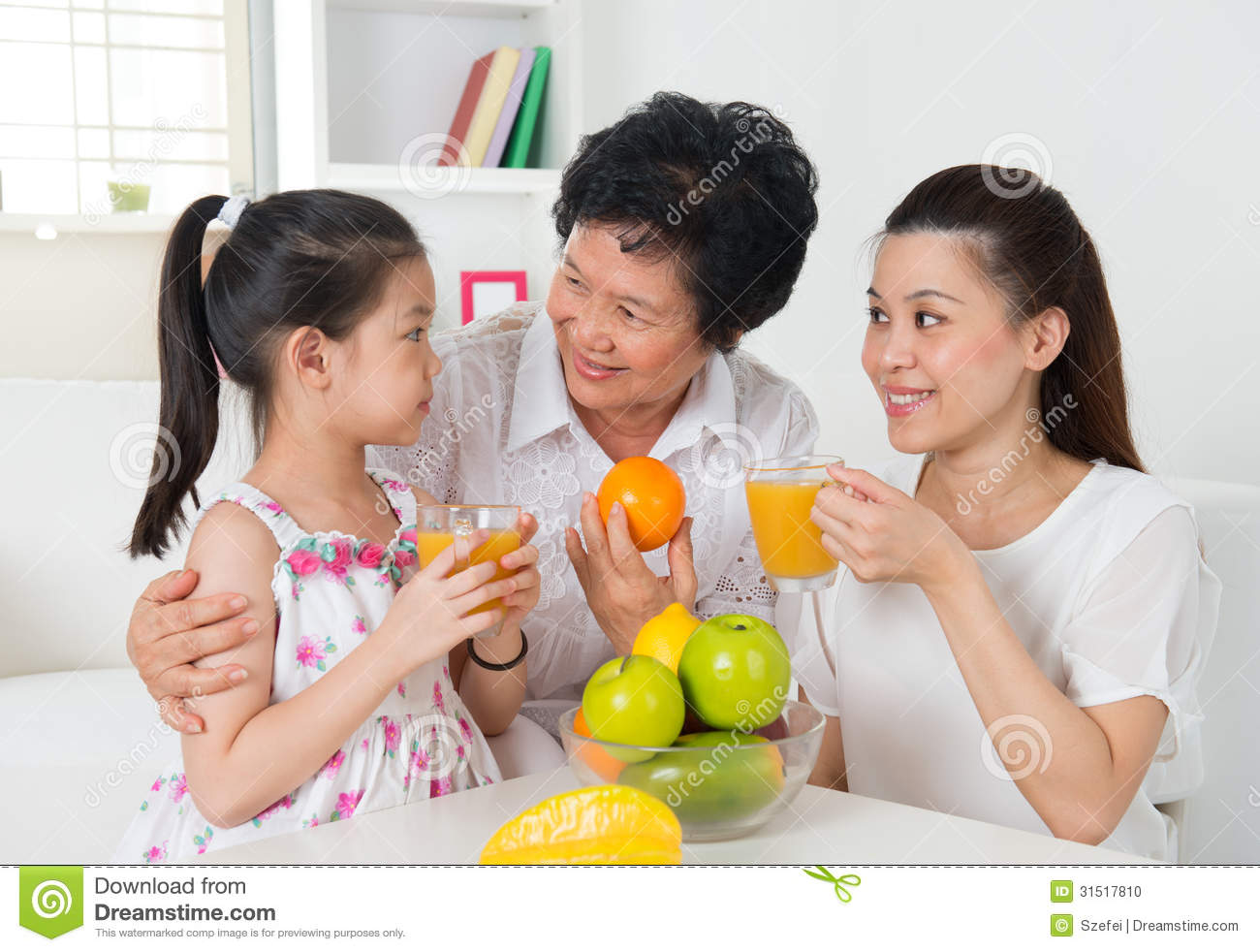 Asian family drinking orange juice. Happy Asian grandparent, parent ...