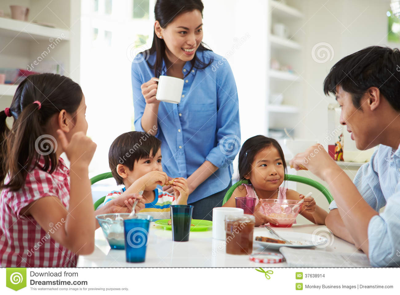 Asian Family Having Breakfast Together In Kitchen Stock