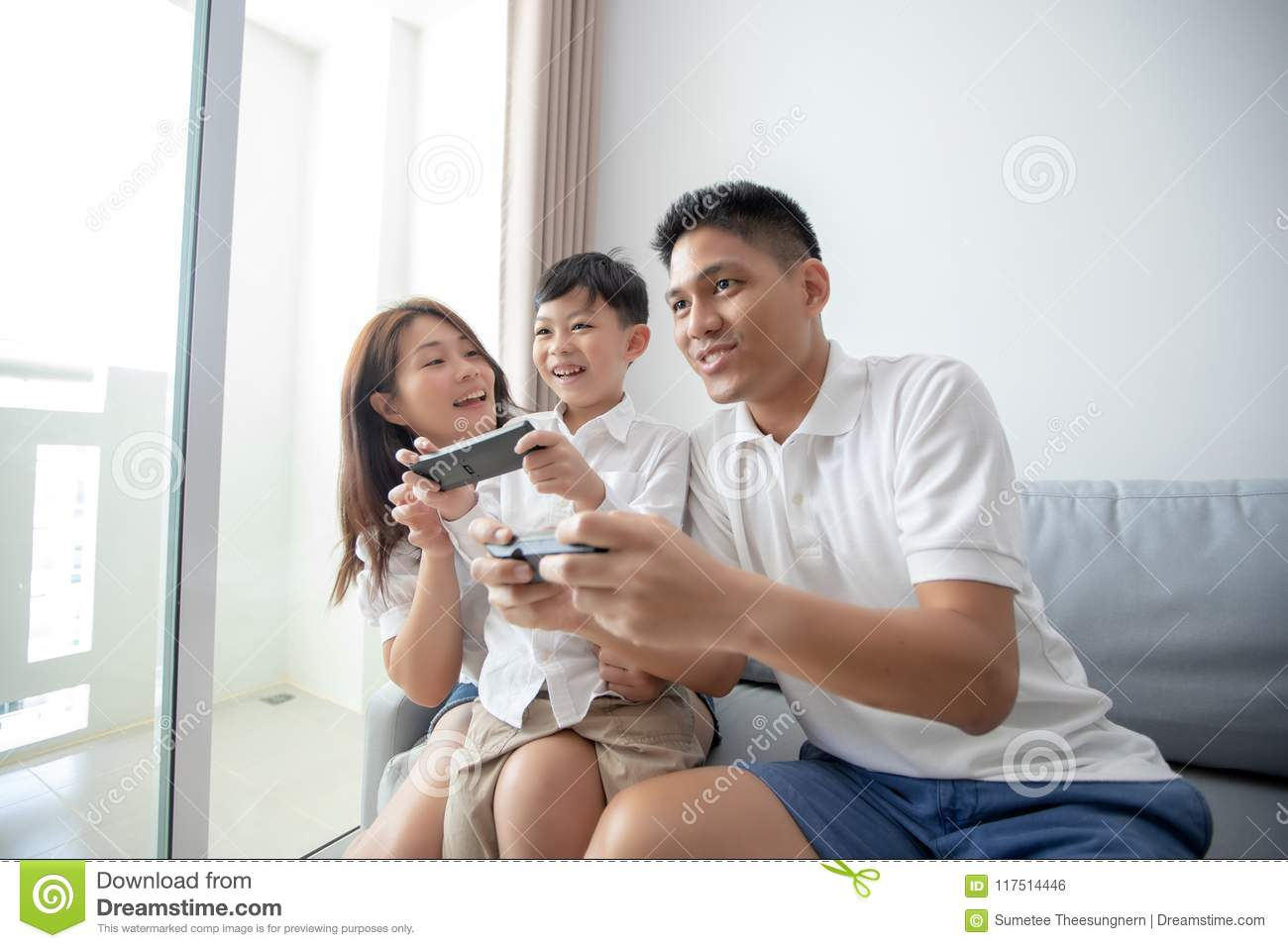 Asian family having fun playing computer console games together, Father and son have the handset controllers and the mother is ch