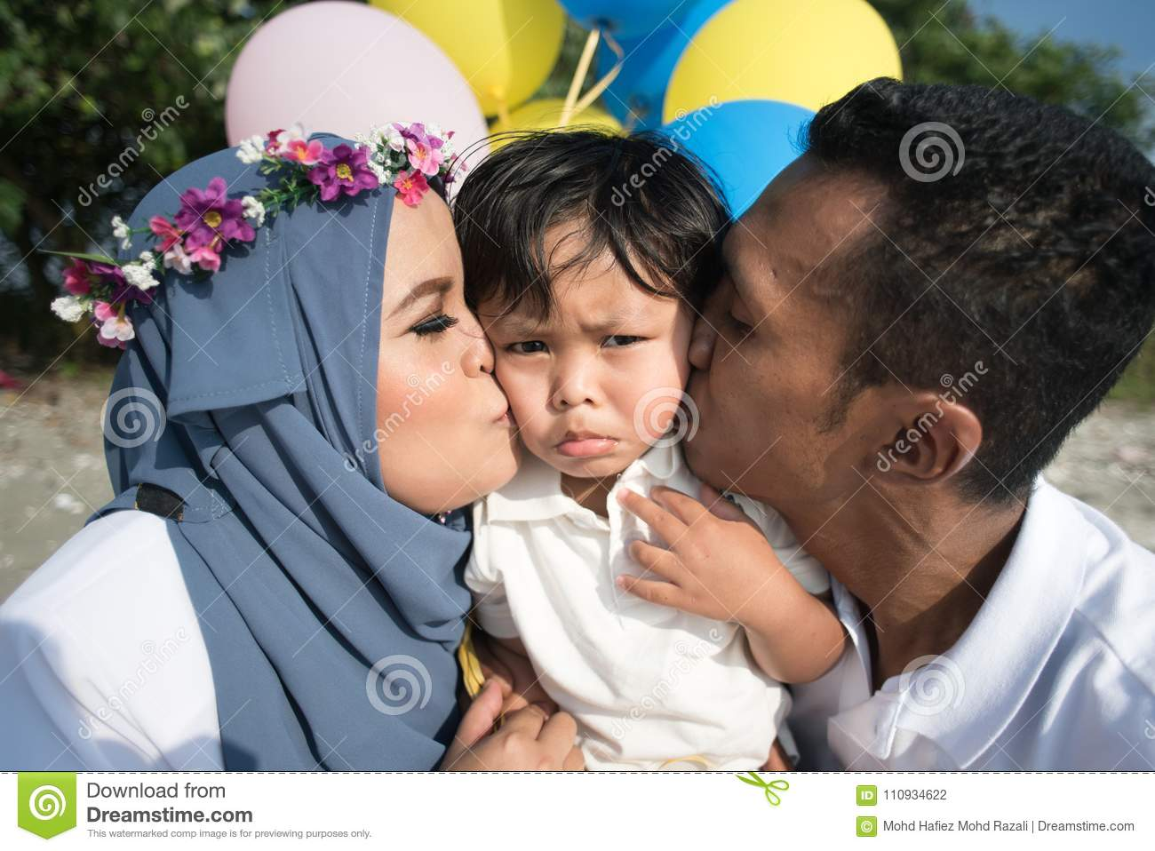 Asian family mother and father kissing their son