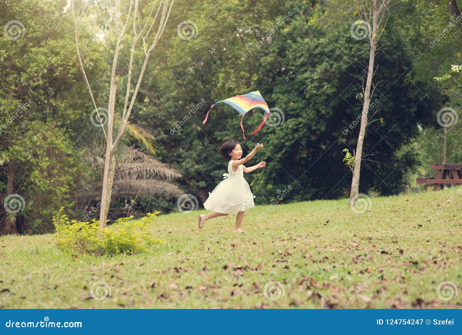 Happy little Asian girl flying kite at park.