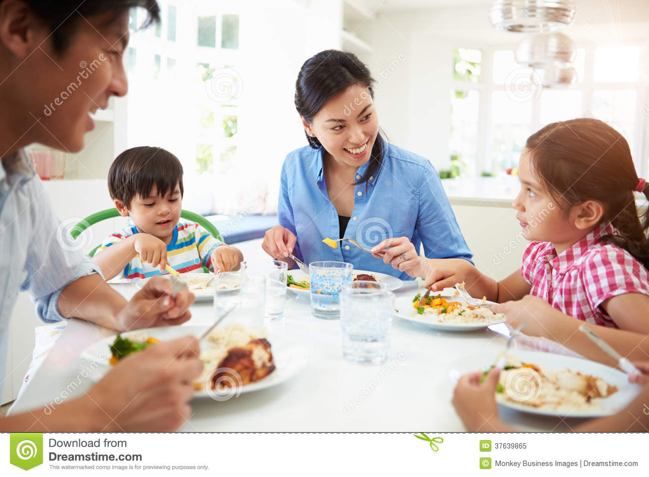 Asian Family Sitting At Table Eating Meal Together Royalty