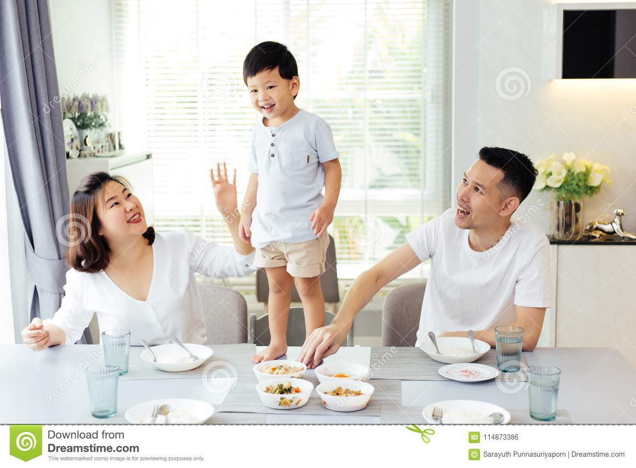 Asian family watching their kid as he is determined and proud to finally stand on the dining table.