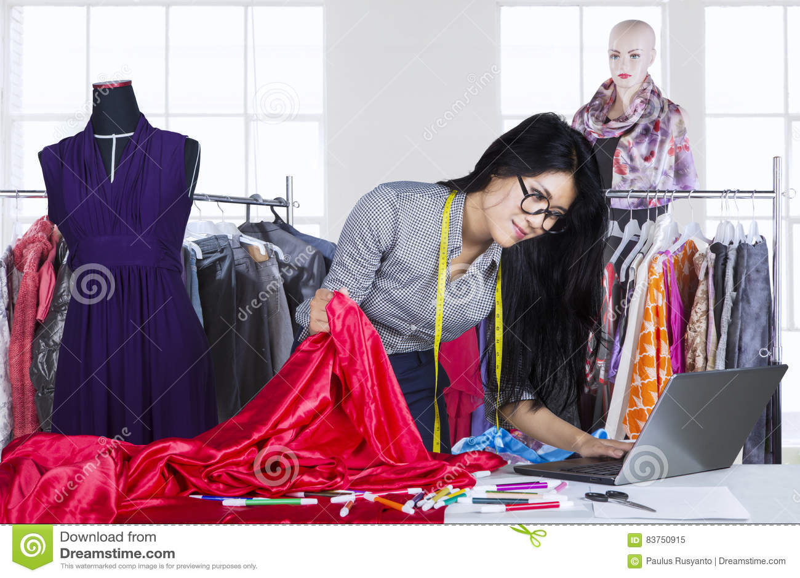 Asian fashion designer working on laptop