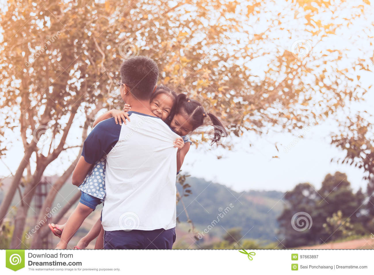 Asian father carrying two child girls and spinning around