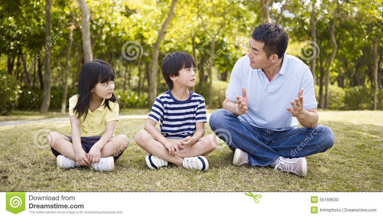 Asian father and children talking in park