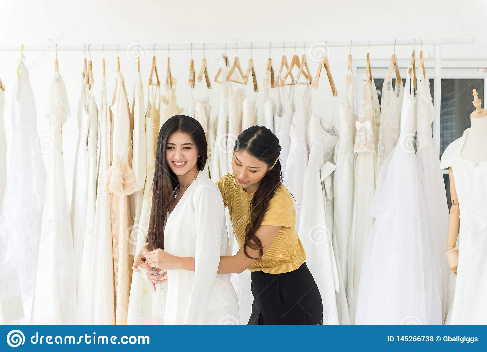 Asian Female Bride Trying On Wedding Dress Woman Designer Making Adjustment With Measuring Tape In Fashion Studio Stock Photo Image Of Friends Dressmaker 145266738