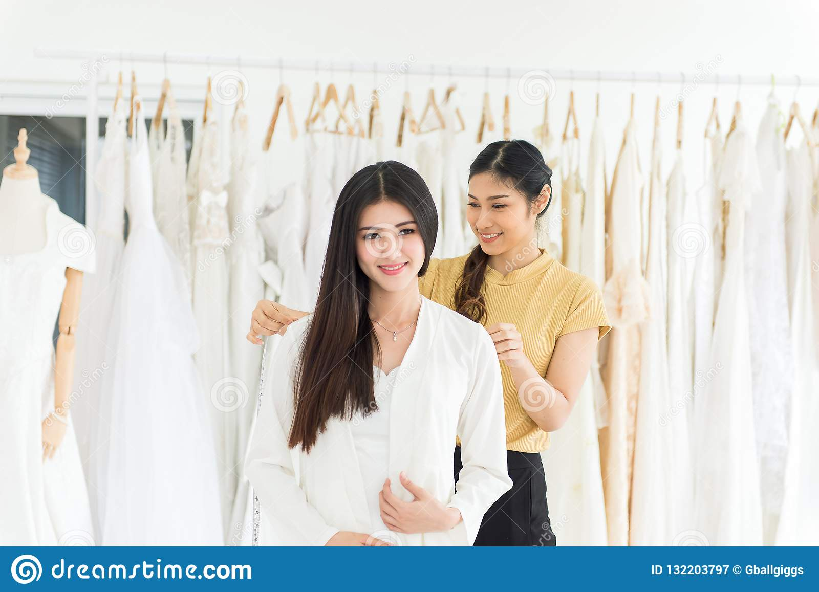 Asian Female Bride Trying On Wedding Dress Woman Designer Making Adjustment With Measuring Tape In Fashion Studio Stock Image Image Of Happy Caucasian 132203797
