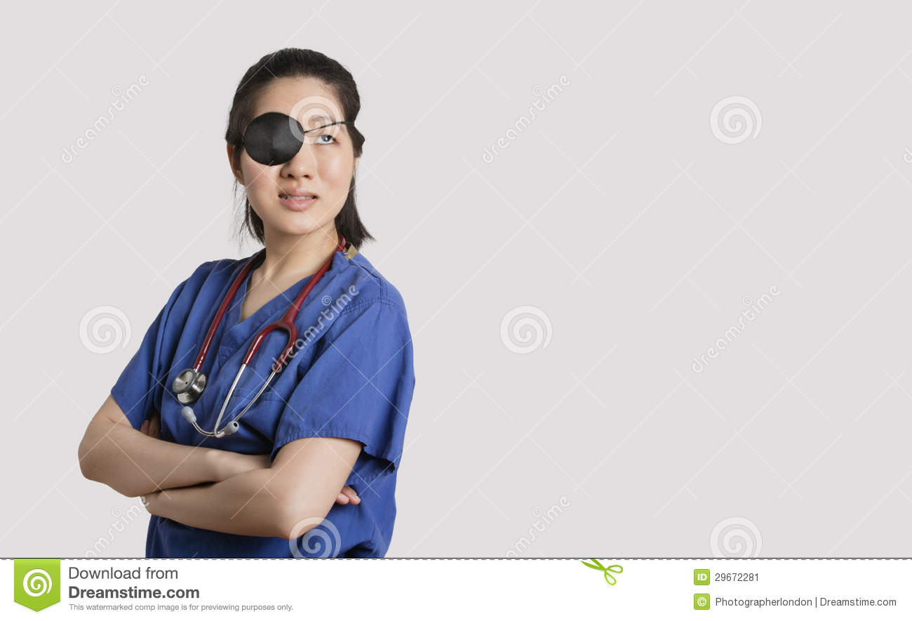 Asian Female Doctor Wearing An Eye Patch Looking Up With