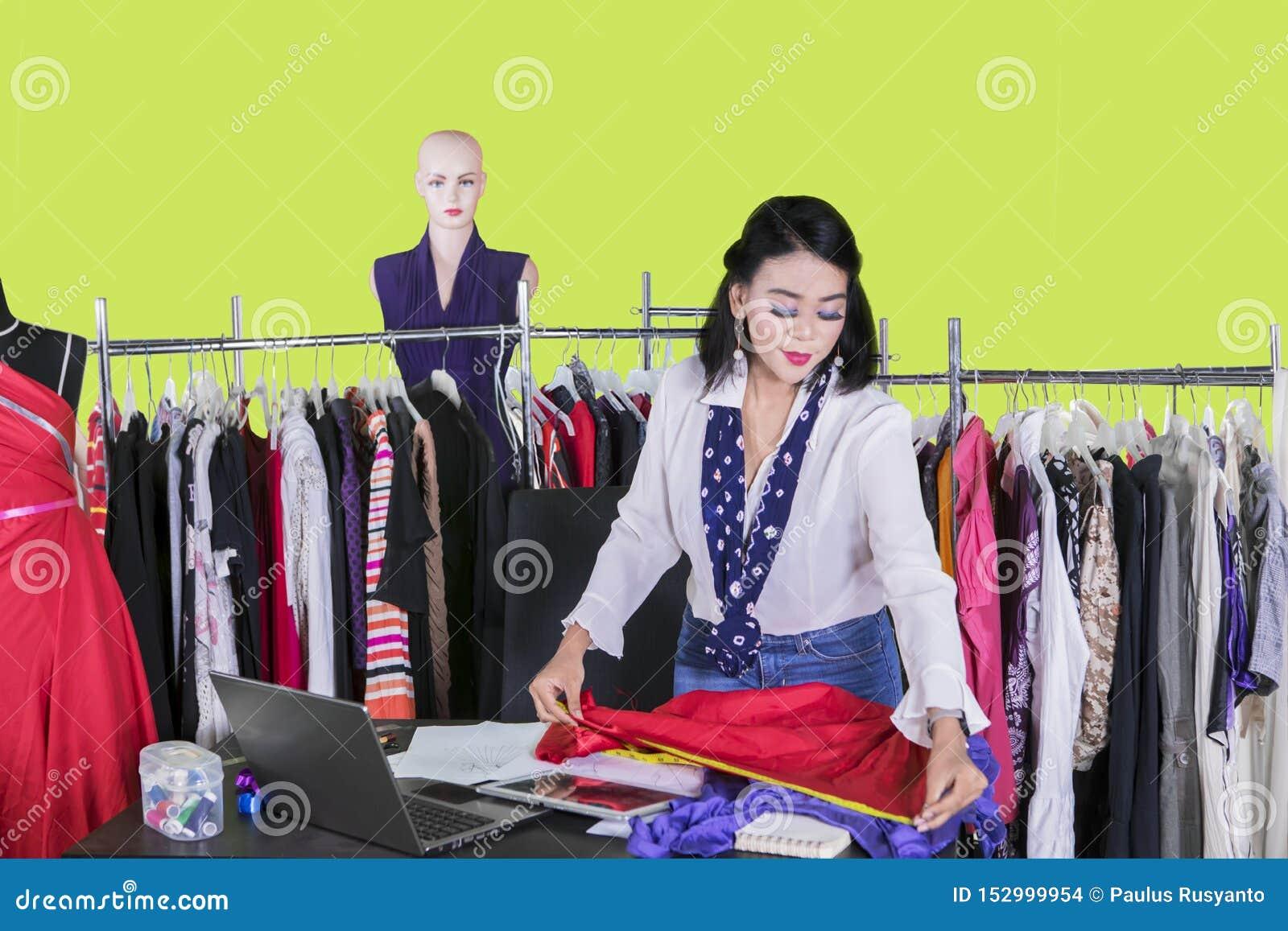 Asian female dressmaker measuring a fabric