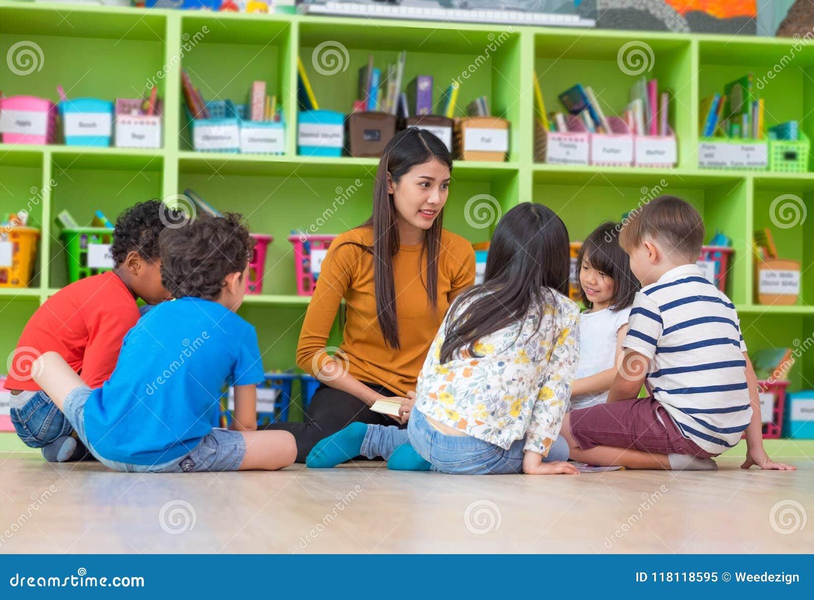 Asian female teacher teaching mixed race diversity group of kids
