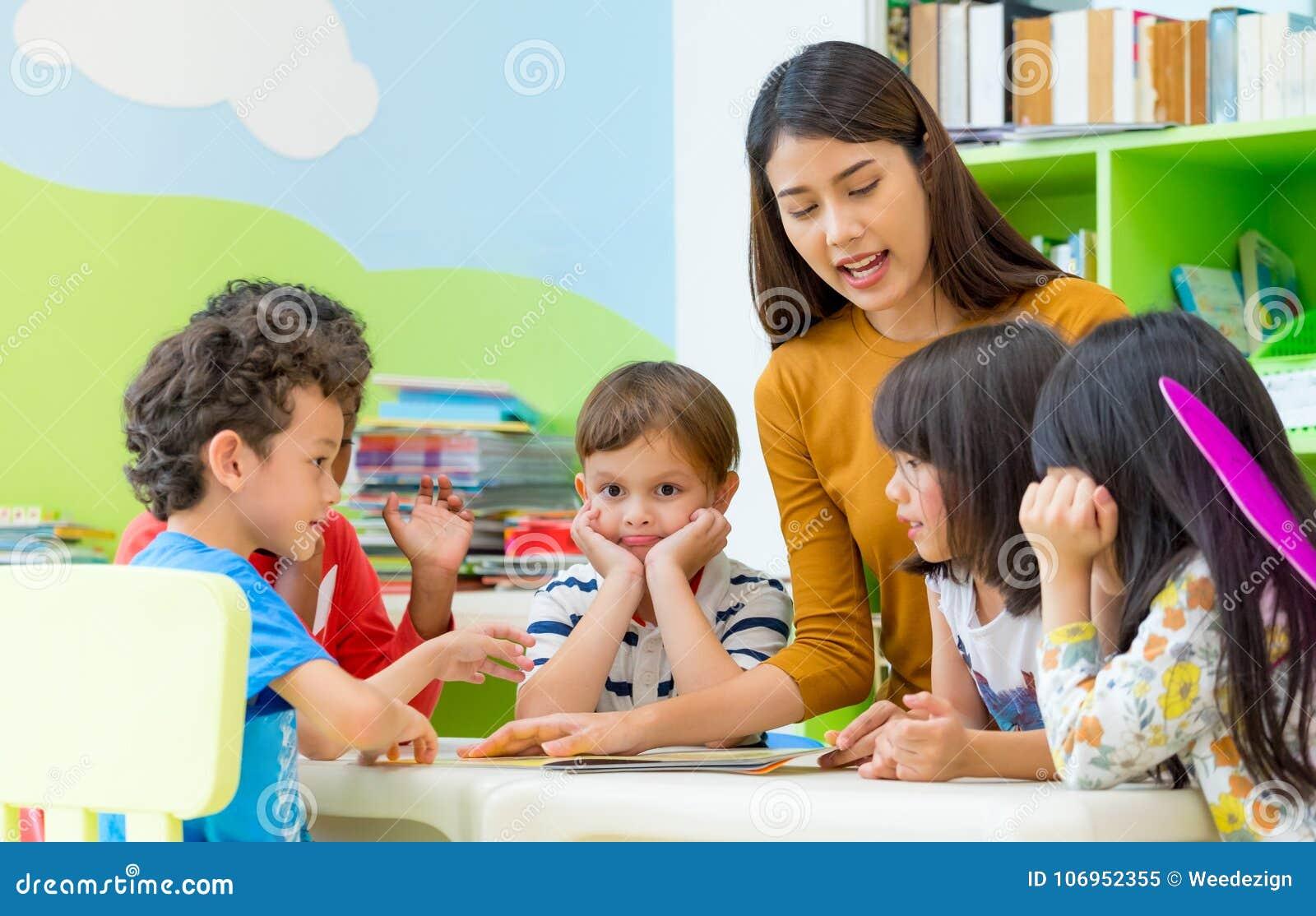 Asian Teacher Teaching Mixed Race Kids Reading Book ... on