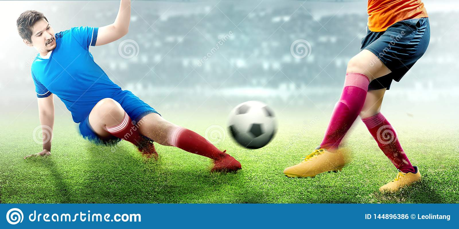 Asian football player man in blue jersey sliding tackle the ball from his opponent