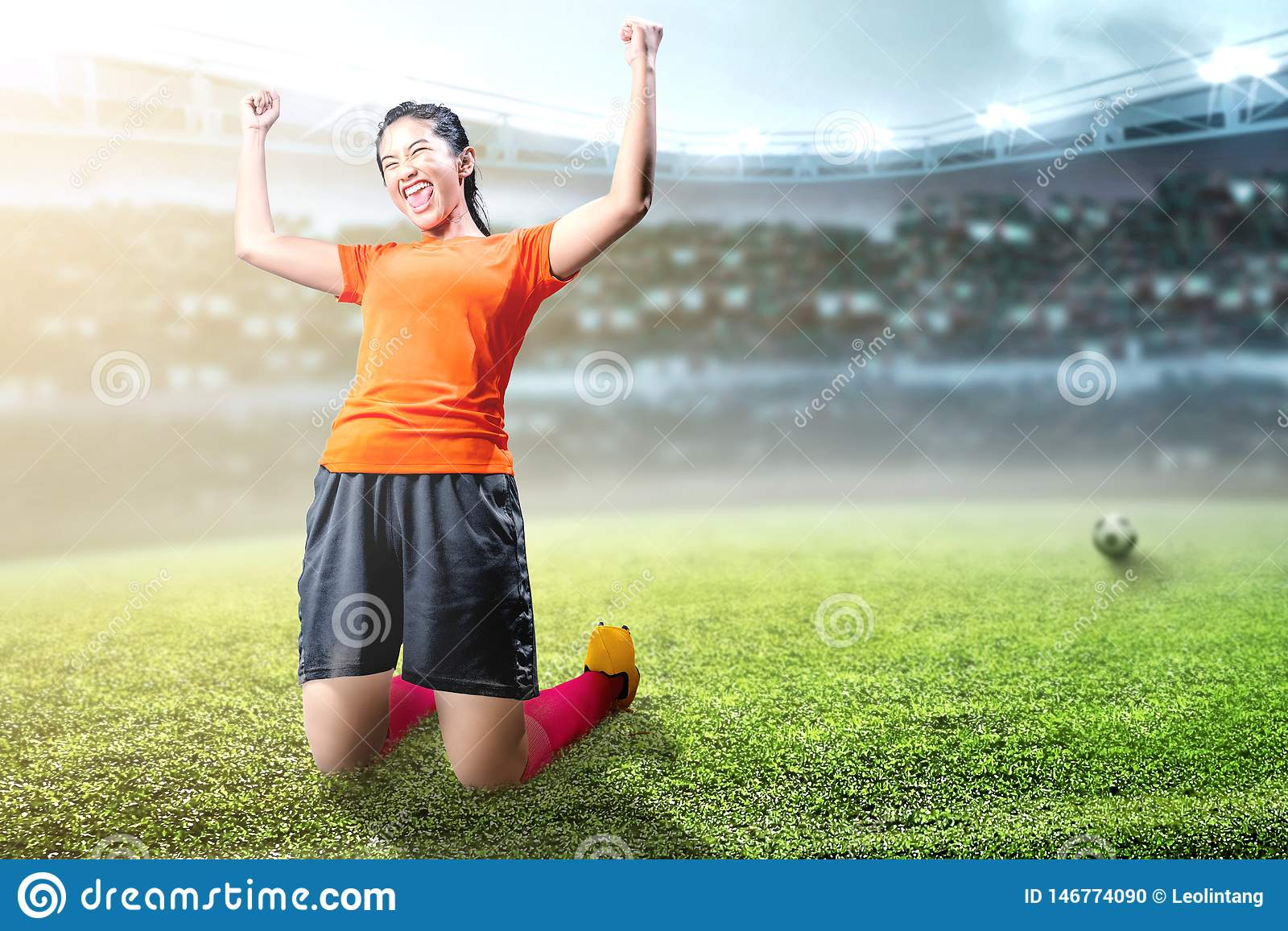 Asian football player woman celebrate her goal with raised arms and kneeling