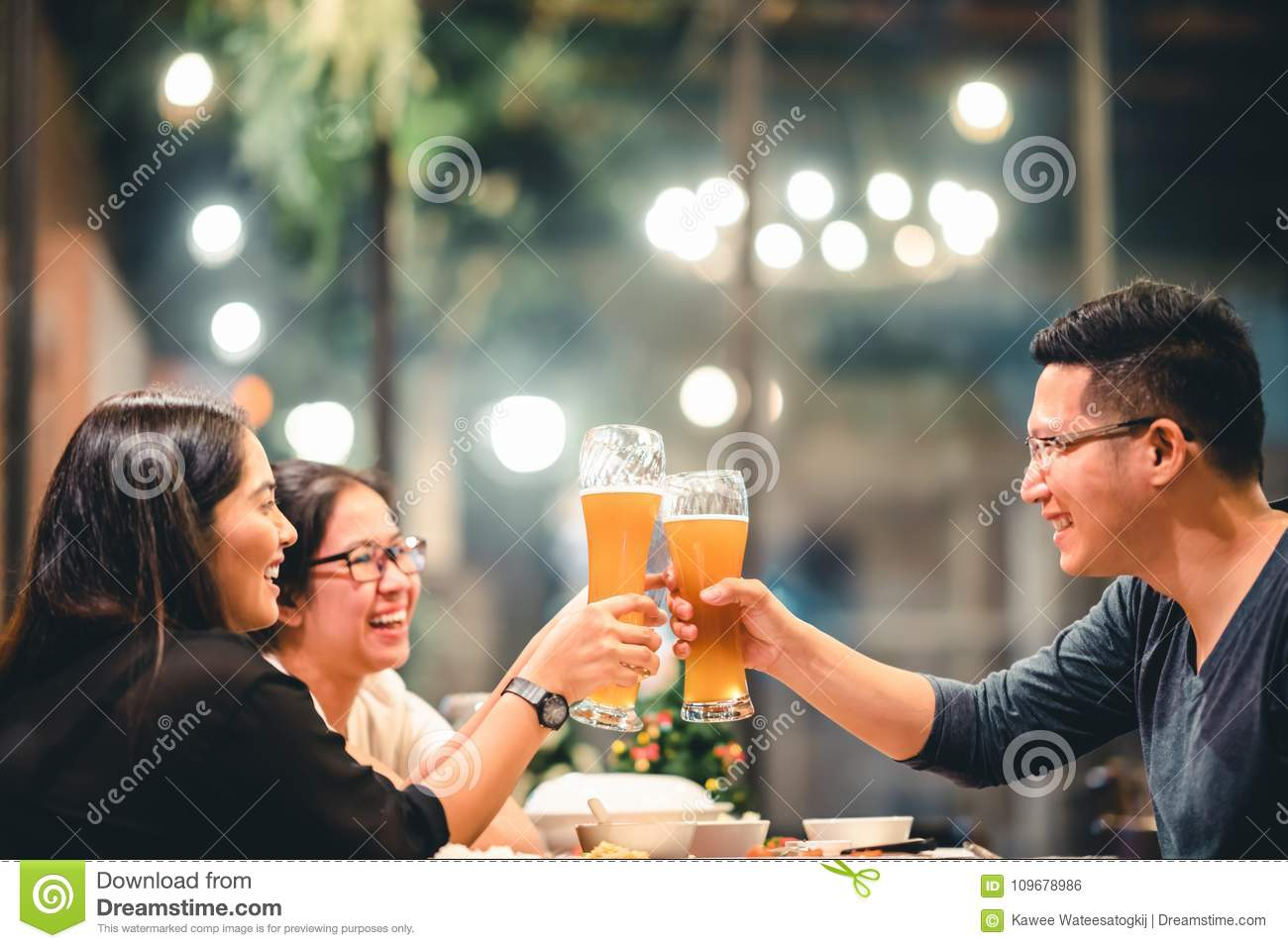 Asian friends or coworkers cheering with beer, celebrating together at restaurant or night club. Young people toasting at party.