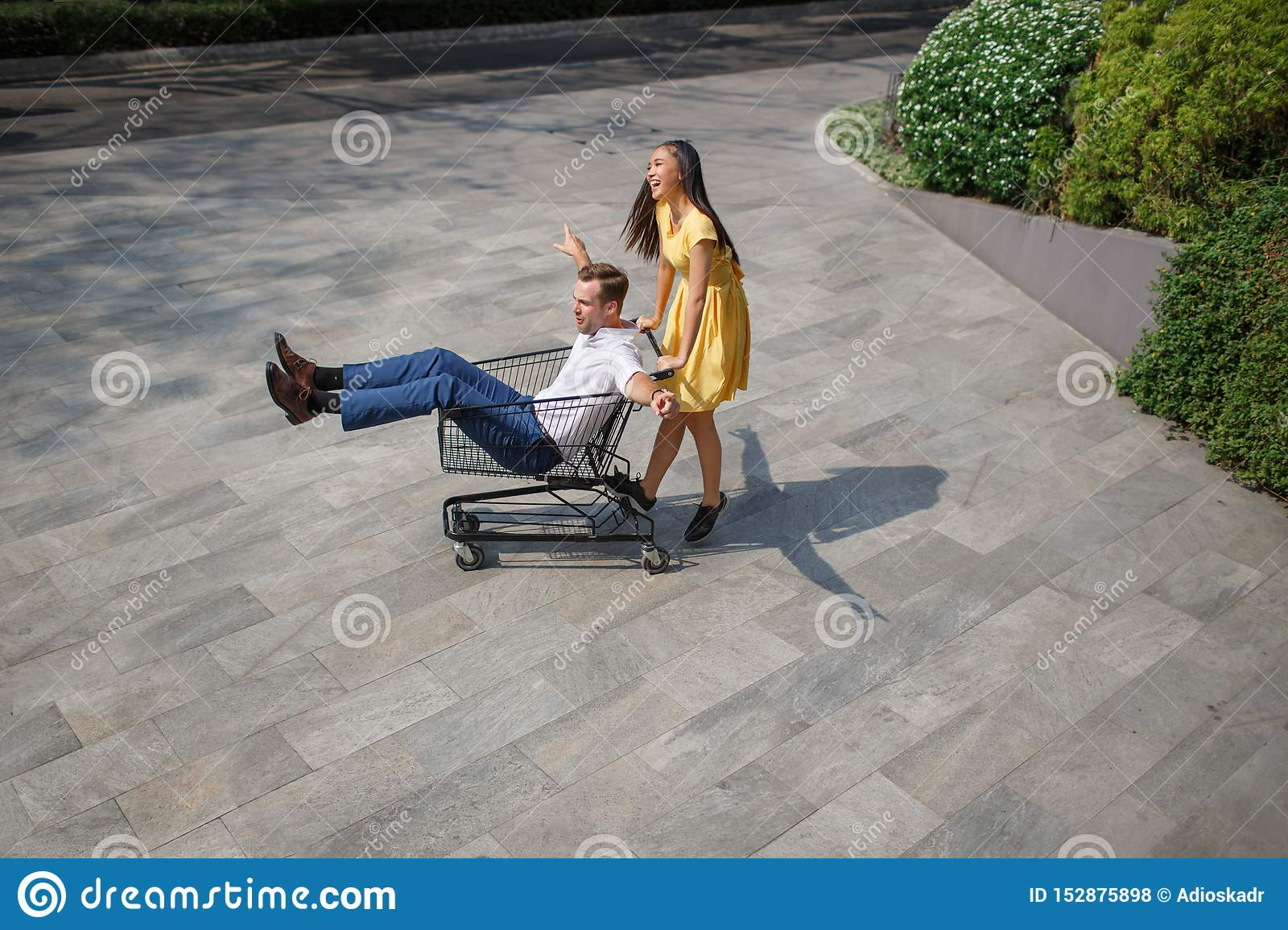 Asian girl and caucasian man together having fun on the street