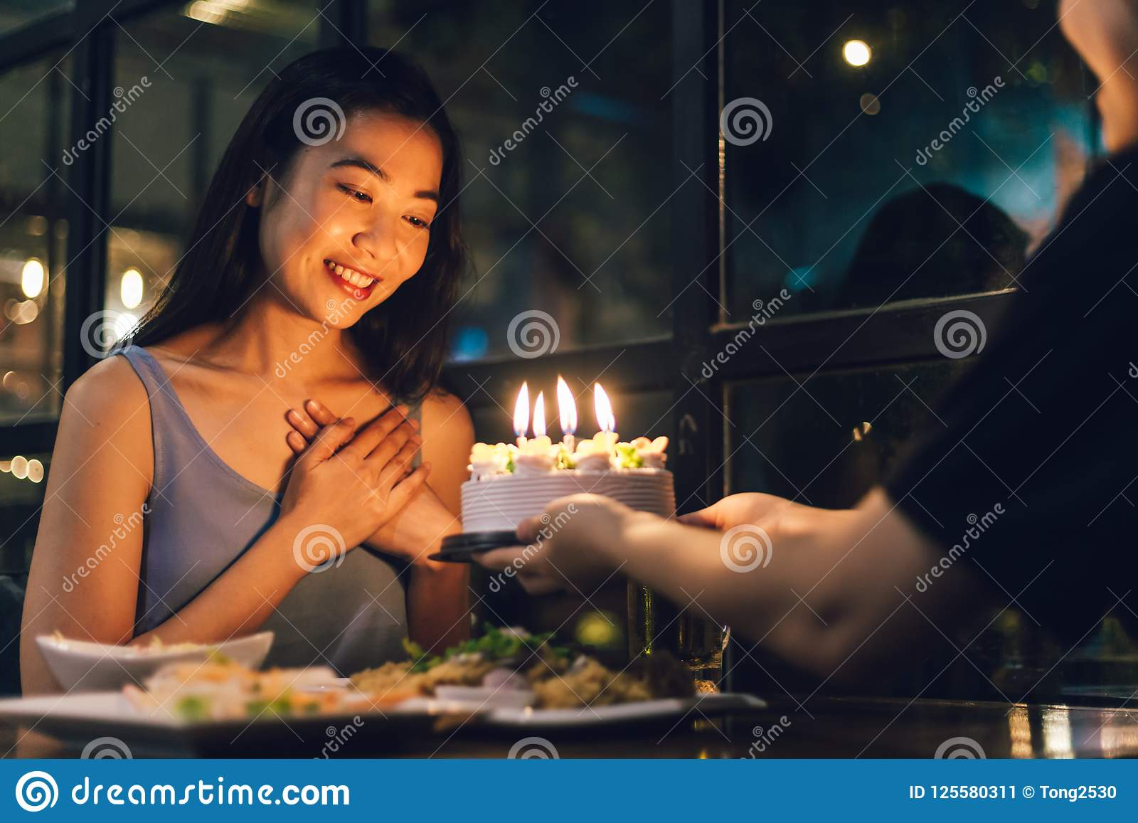 Asian girl impresses with her birthday cake in the night of happiness.