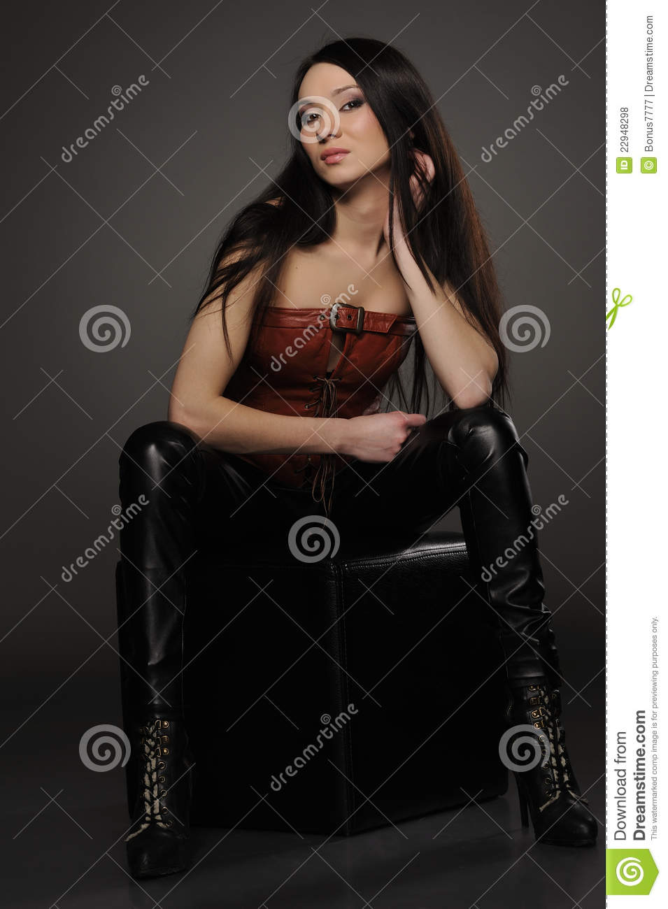8aee6b27 Beautiful asian girl in leather pants and corset sitting on black cube