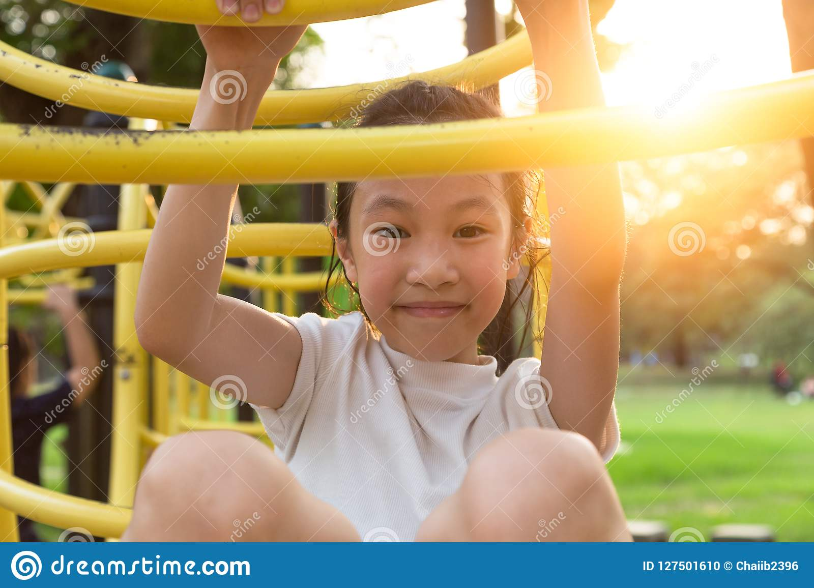 Happy,Asian little girl playing on a playground outdoor and looking at camera in the park,summer,vacation concept