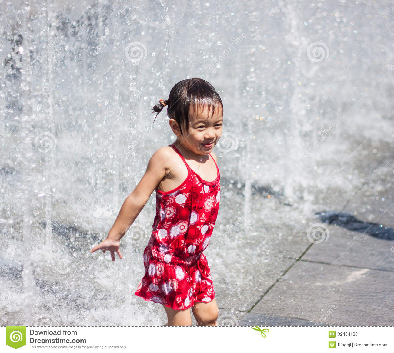 a asian girl playing by water fountain editorial photo
