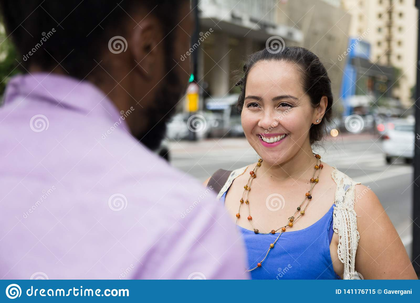 Asian girl talking to african american friend in the streets
