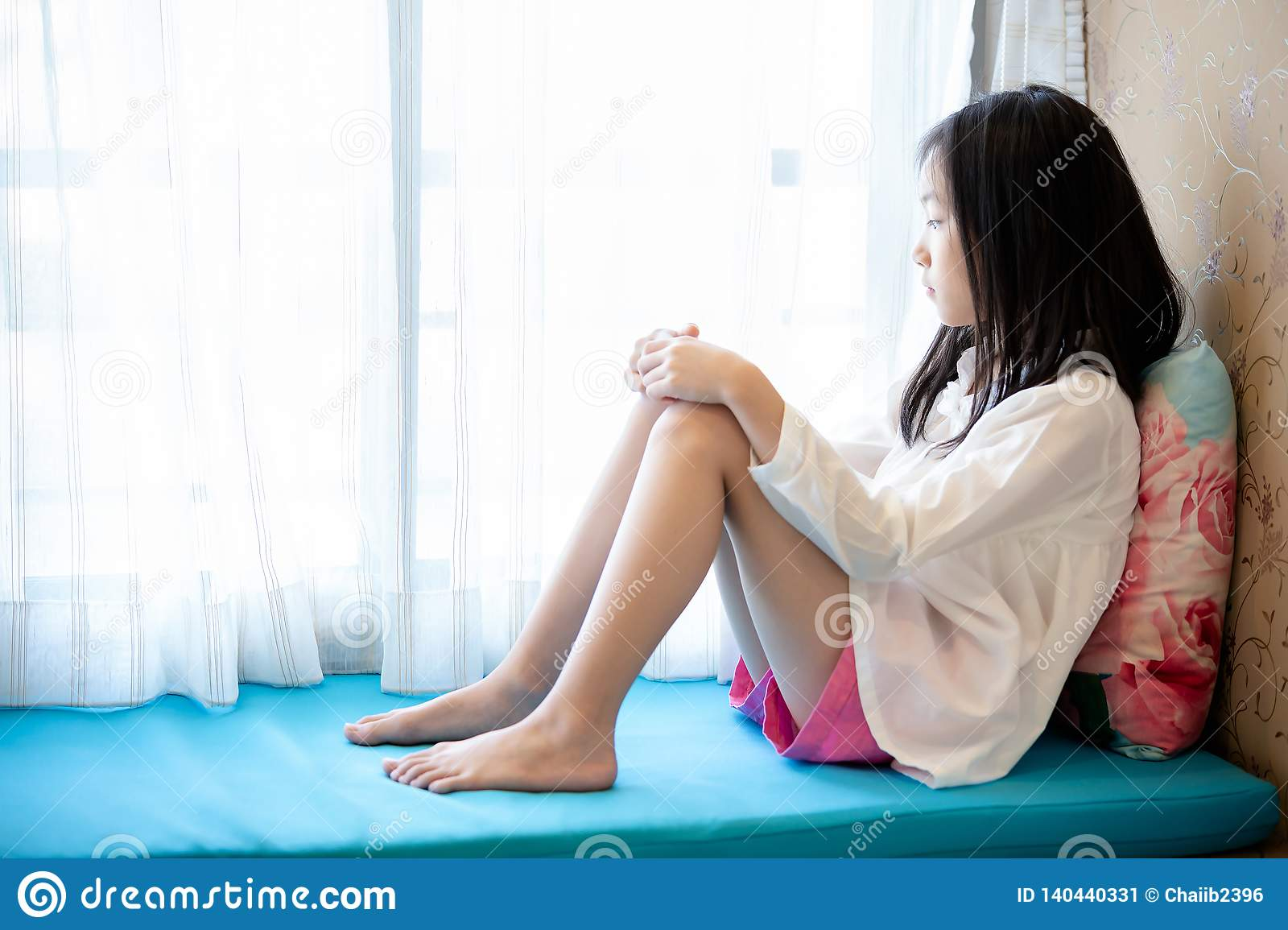Asian girl waiting,sitting and looking at the window in home