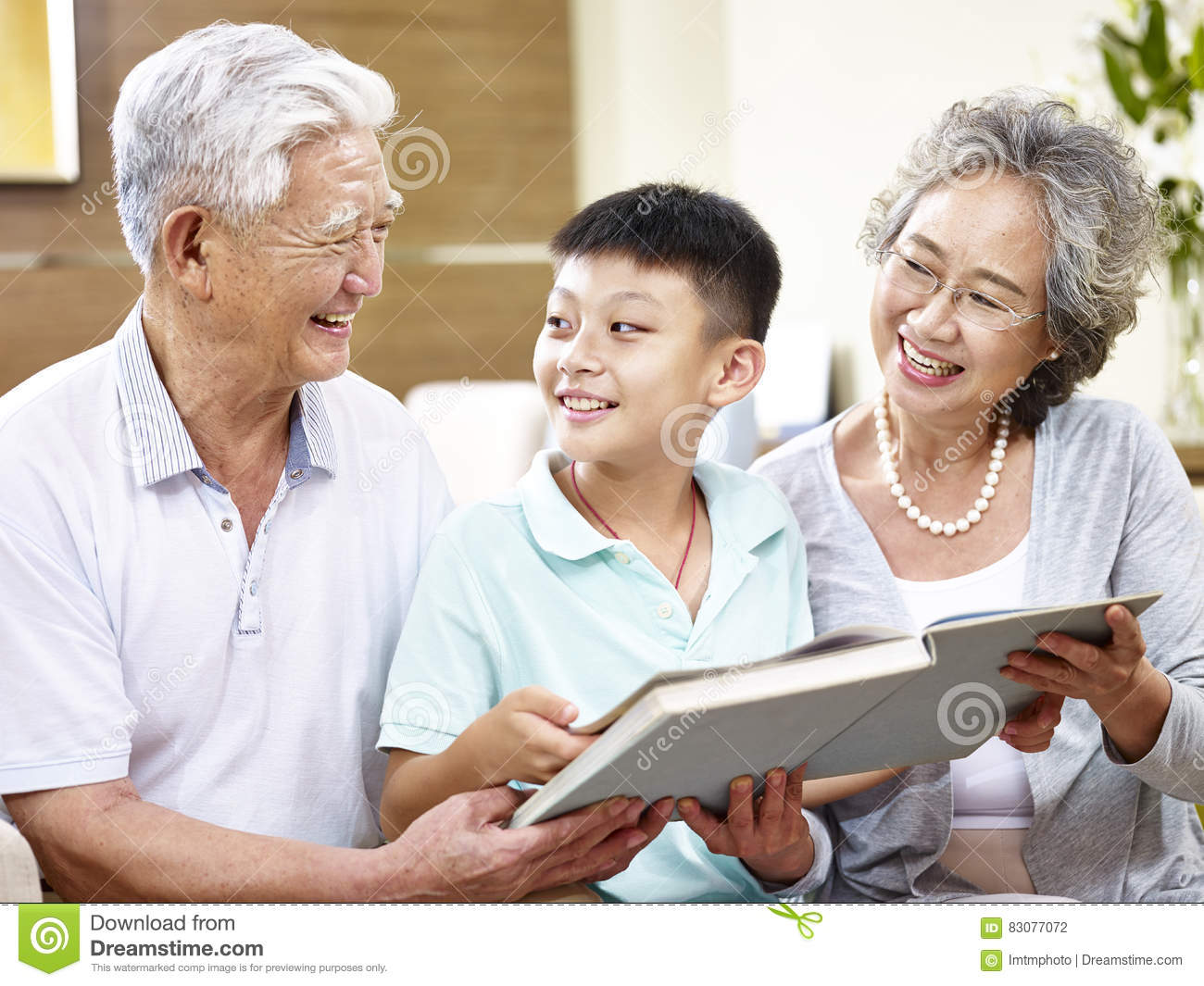asian grandparents and grandchild reading a book together stock