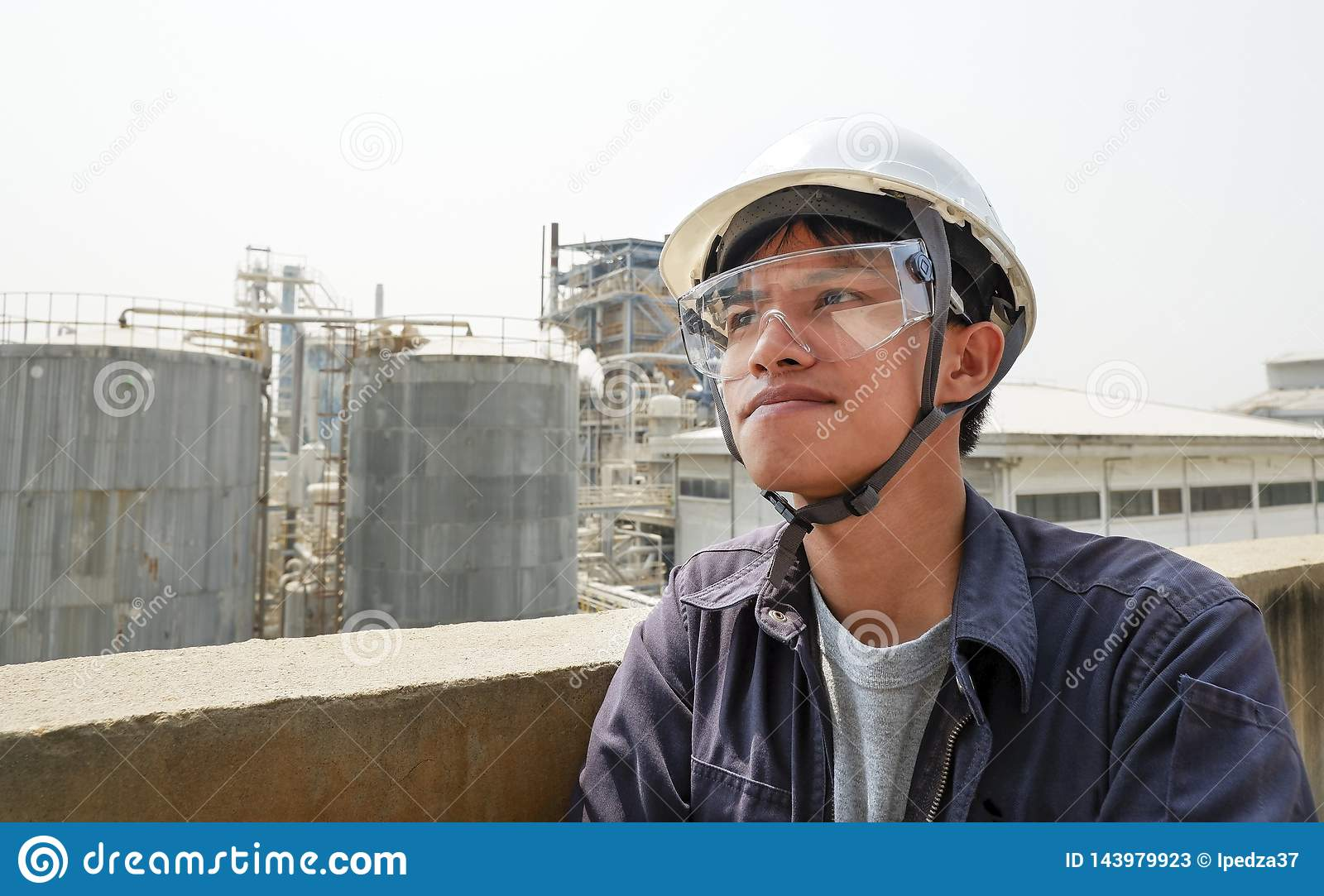 Asian guy Wearing a helmet Working in a large industrial factory Checking the production process