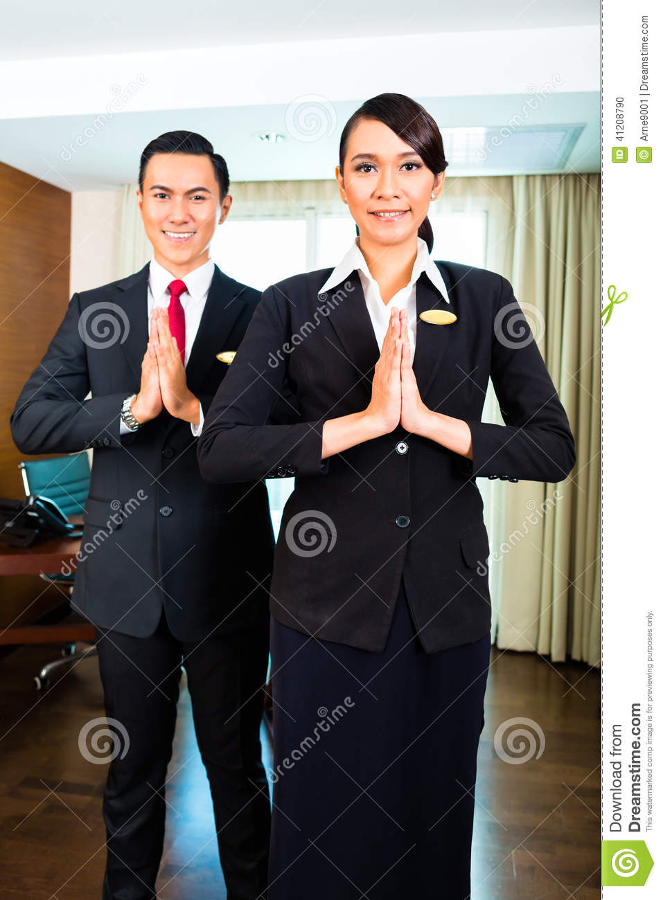 Asian Hotel Staff Greeting With Hands Put Together Stock