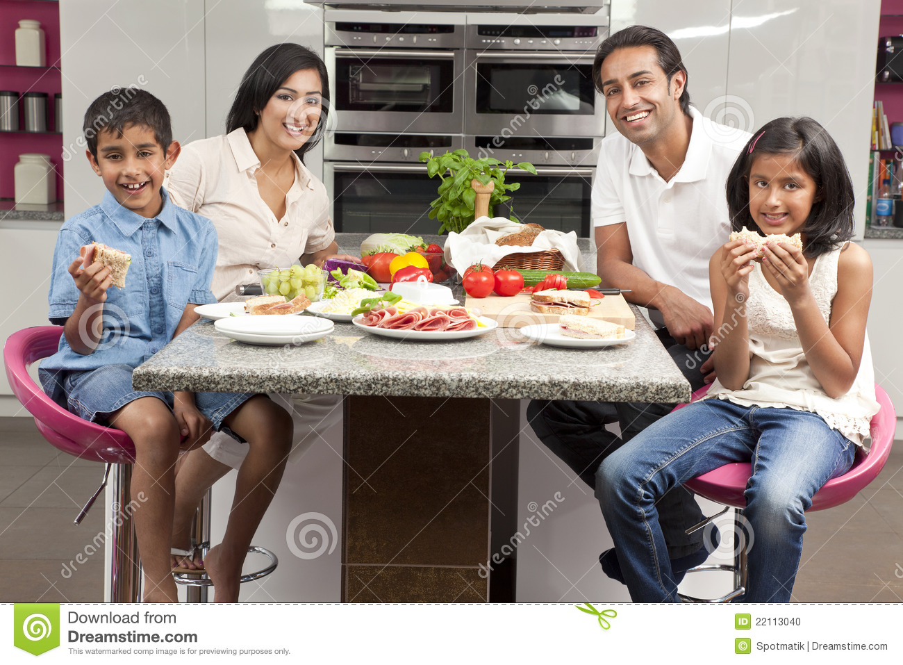 An attractive happy, smiling Asian Indian family of mother, father, son and  daughter eating healthy food & salad in the kitchen at home