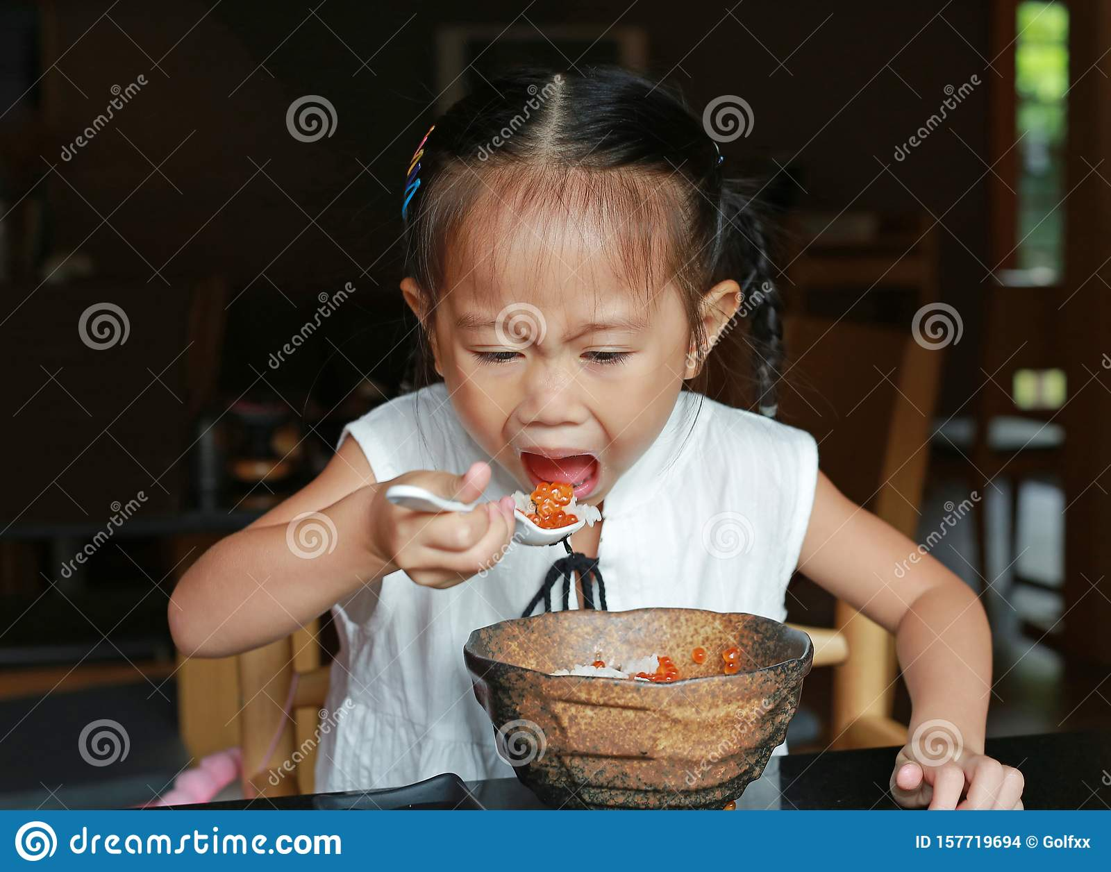 Asian kid girl eating delicious food on table for lunch in the restaurant