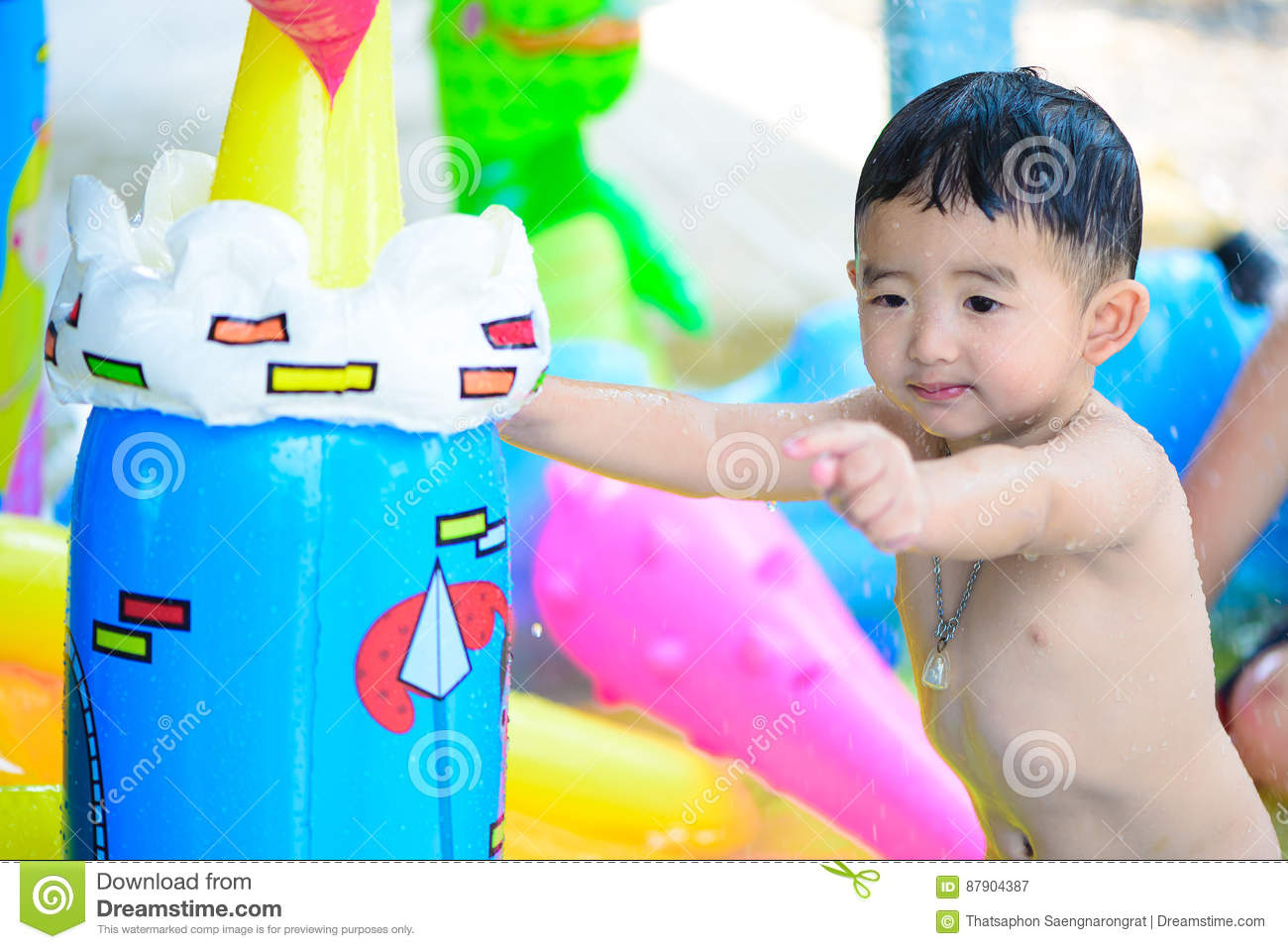 Asian kid playing in inflatable baby swimming pool on hot summer